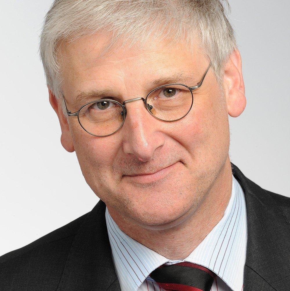 Ein älterer Mann mit Brille und grauen, kurzen Haaren.