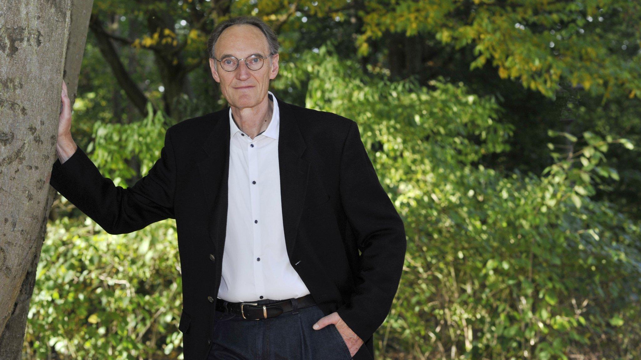 Bild von Dr. Henning Engeln im Format 16zu 9. Die Aufnahme zeigt ihn im Freien in einer parkähnlichen Landschaft stehend, die rechte Hand an einen mächtigen Baum gelehnt. Der Wissenschaftsjournalist, Biologe und Buchautor war viele Jahre lang Redakteur bei GEO und ist jetzt Mitglied der Riffreporter eG.