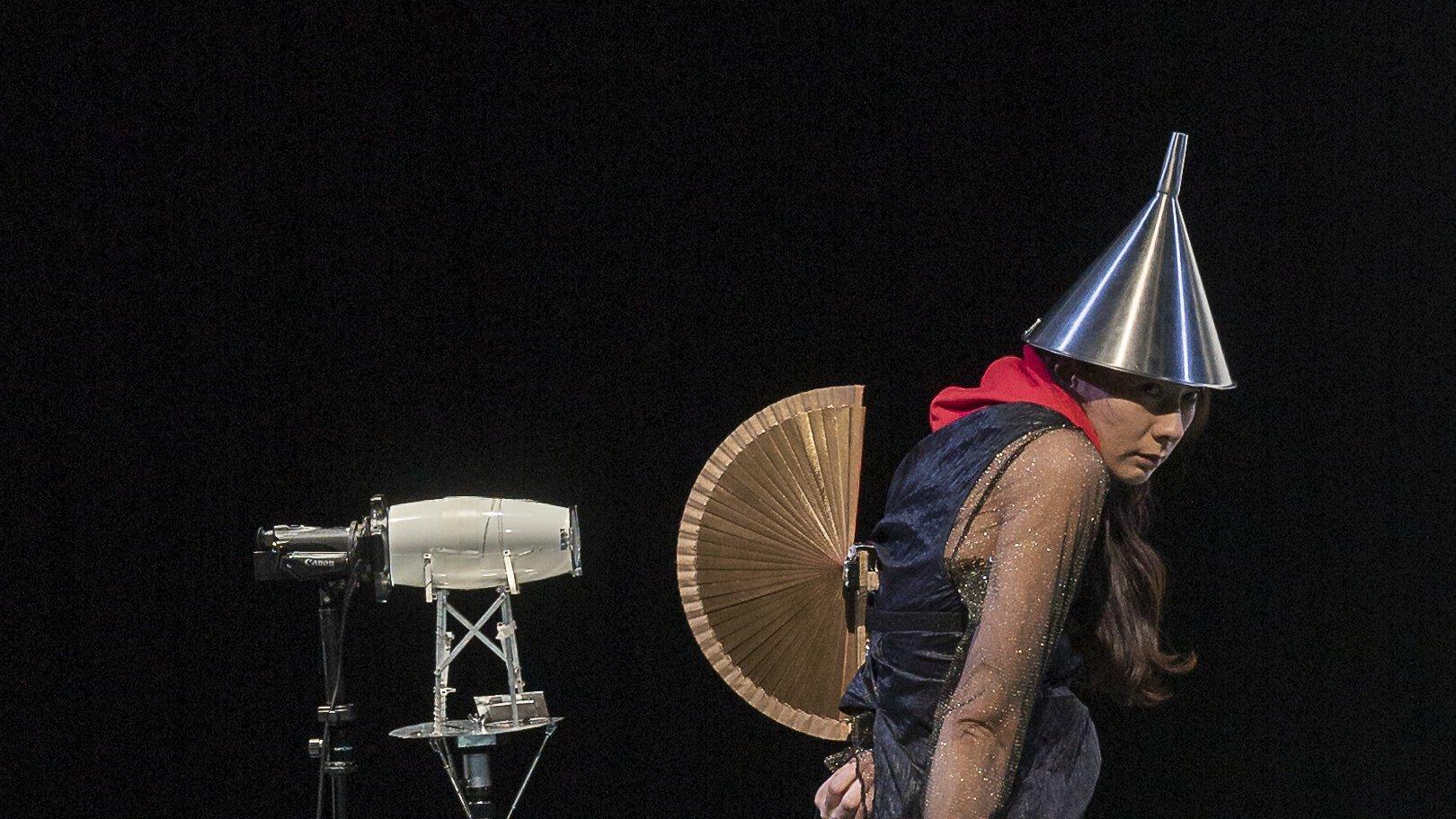 Die Darstellerin Elisabeth Hofmann steht auf der Bühne, als sei sie eine Figur aus einem Bild von Hieronymus Bosch. Sie trägt einen Trichter auf dem Kopf und einen geöffneten Fächer auf dem Rücken, wie eine Eidechse mit aufgeplustertem Kamm.