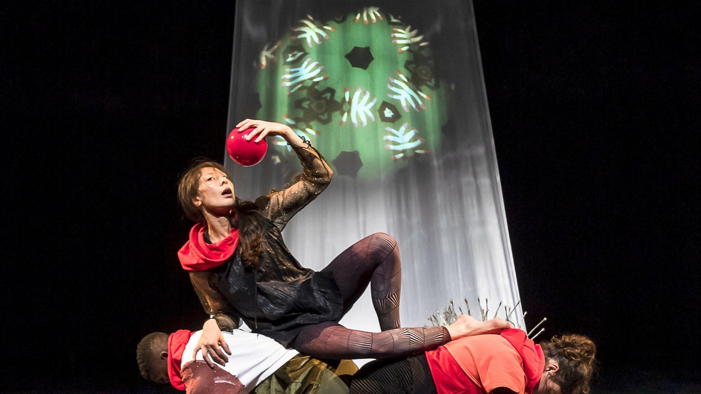 Ein Bild wie aus der Renaissance: Auf dem Rücken von zwei Darsteller:innen hält sich eine weitere Darstellerin einen roten Ball wie eine süße Frucht über ihren geöffneten Mund hält. Im Hintergrund ein weißer Vorhang mit der grünen Projektion eines Kaleidoskops.