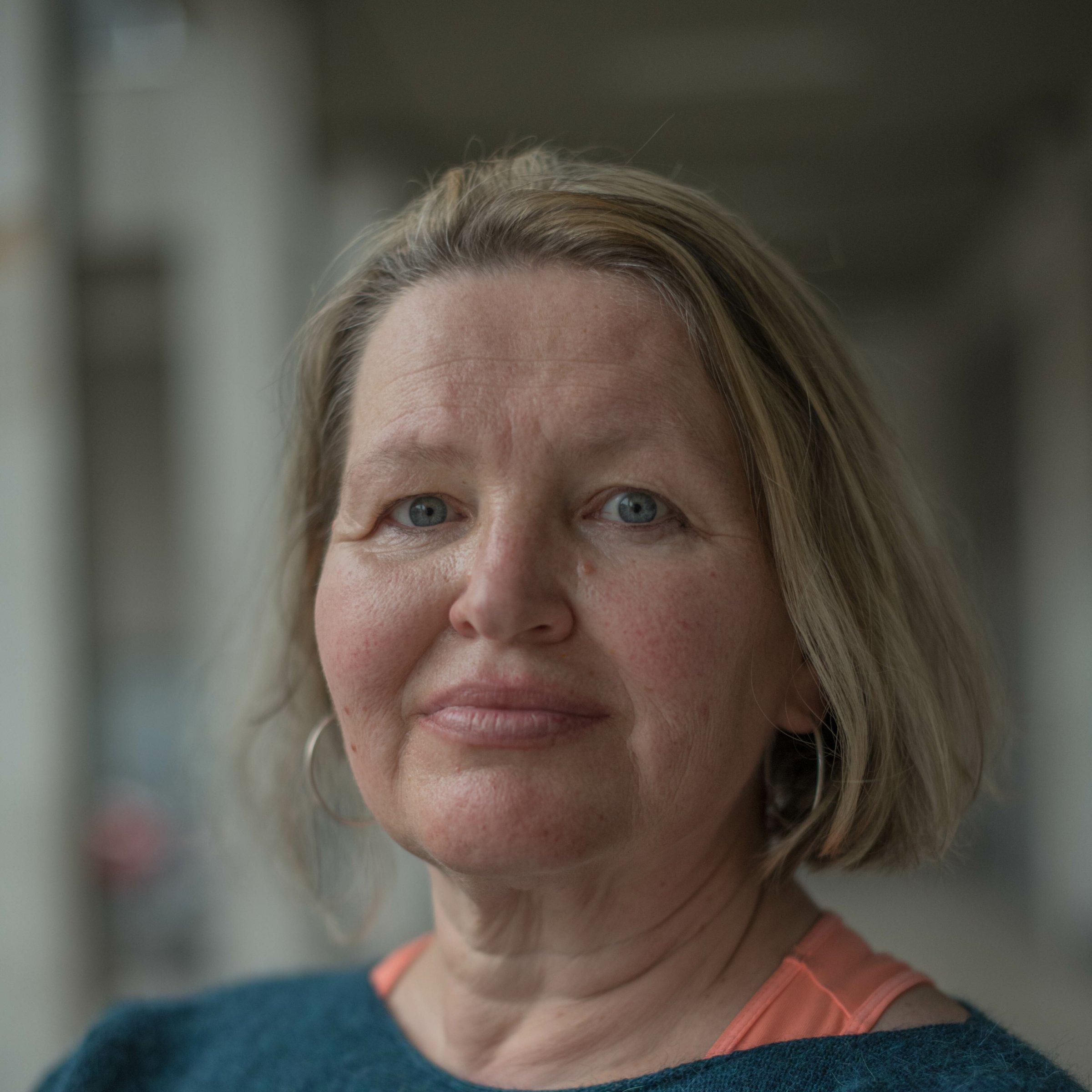 Portrait einer europäisch aussehenden Frau mittleren Alters, blonde kurze Haare.