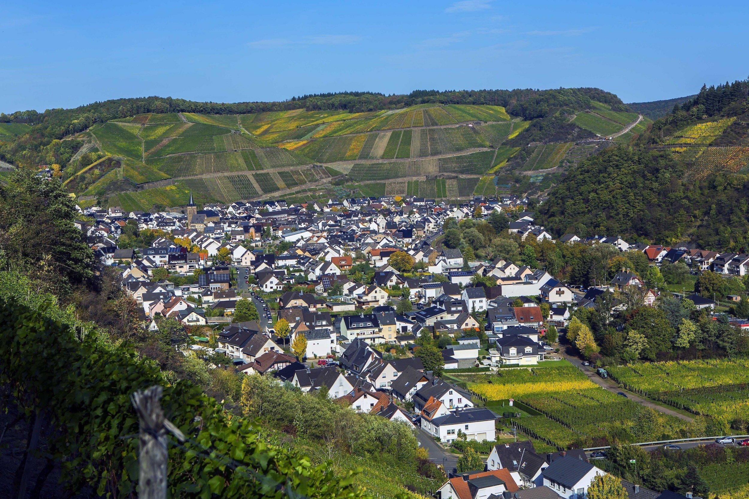 Die Ortschaft liegt dicht gedrängt im engen Tal, umgeben von Weinbergen.