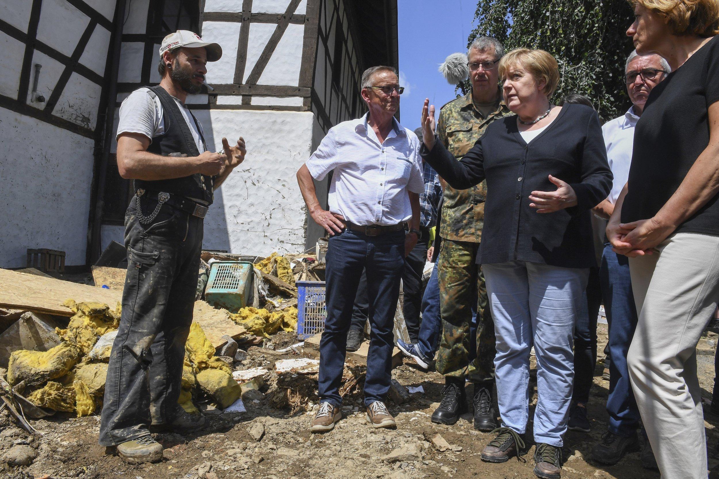 Bundeskanzlerin Angela Merkel beim Gespräch vor einem zerstörten Haus