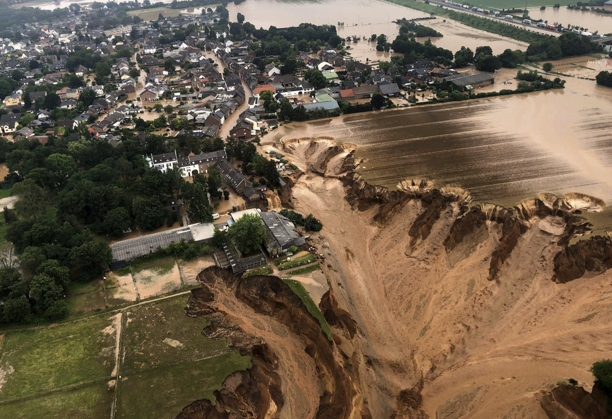 Luftaufnahme von Blessem: Felder und der Rand der Siedlung sind einer großen Abbruchkante gewichen, Wasser fließt hinab in die Sandgrube.