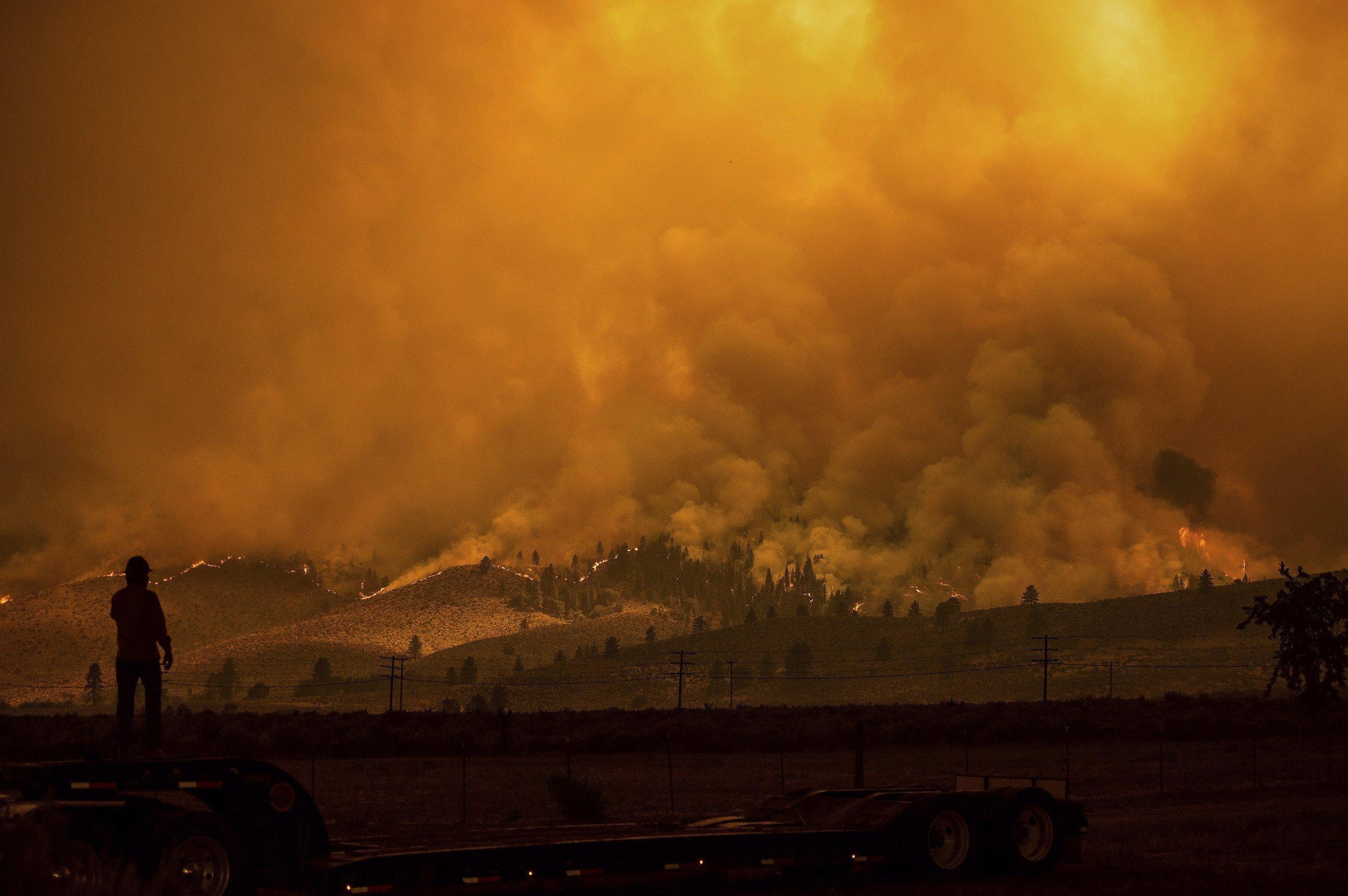 Mann blickt auf brennende Hügelkette