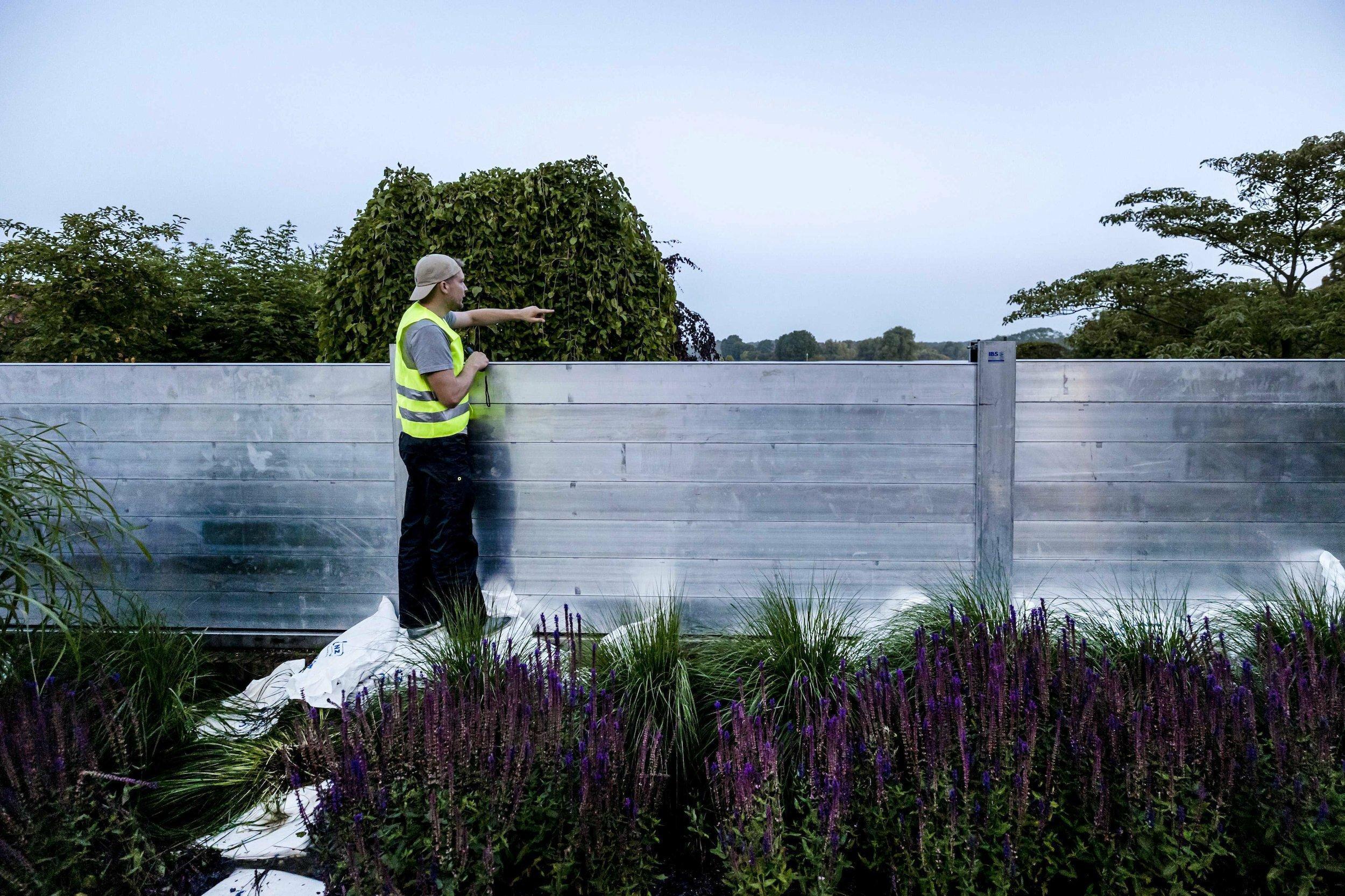 Ein Mann steht vor einer Aluwand auf einer Leiter und deutet auf das dahinterliegende Wasser
