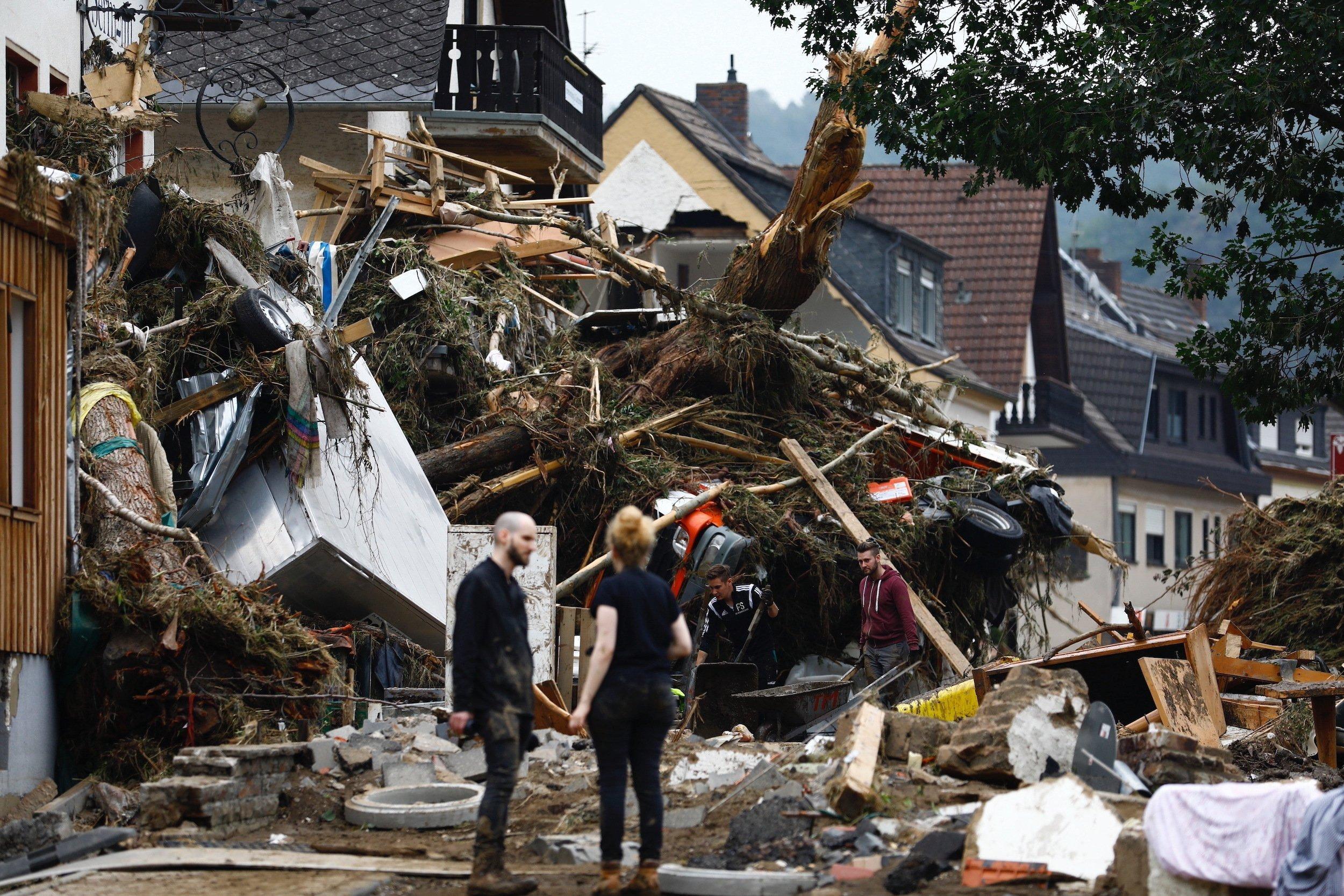 2junge Menschen stehen vor einem zerstörten Haus
