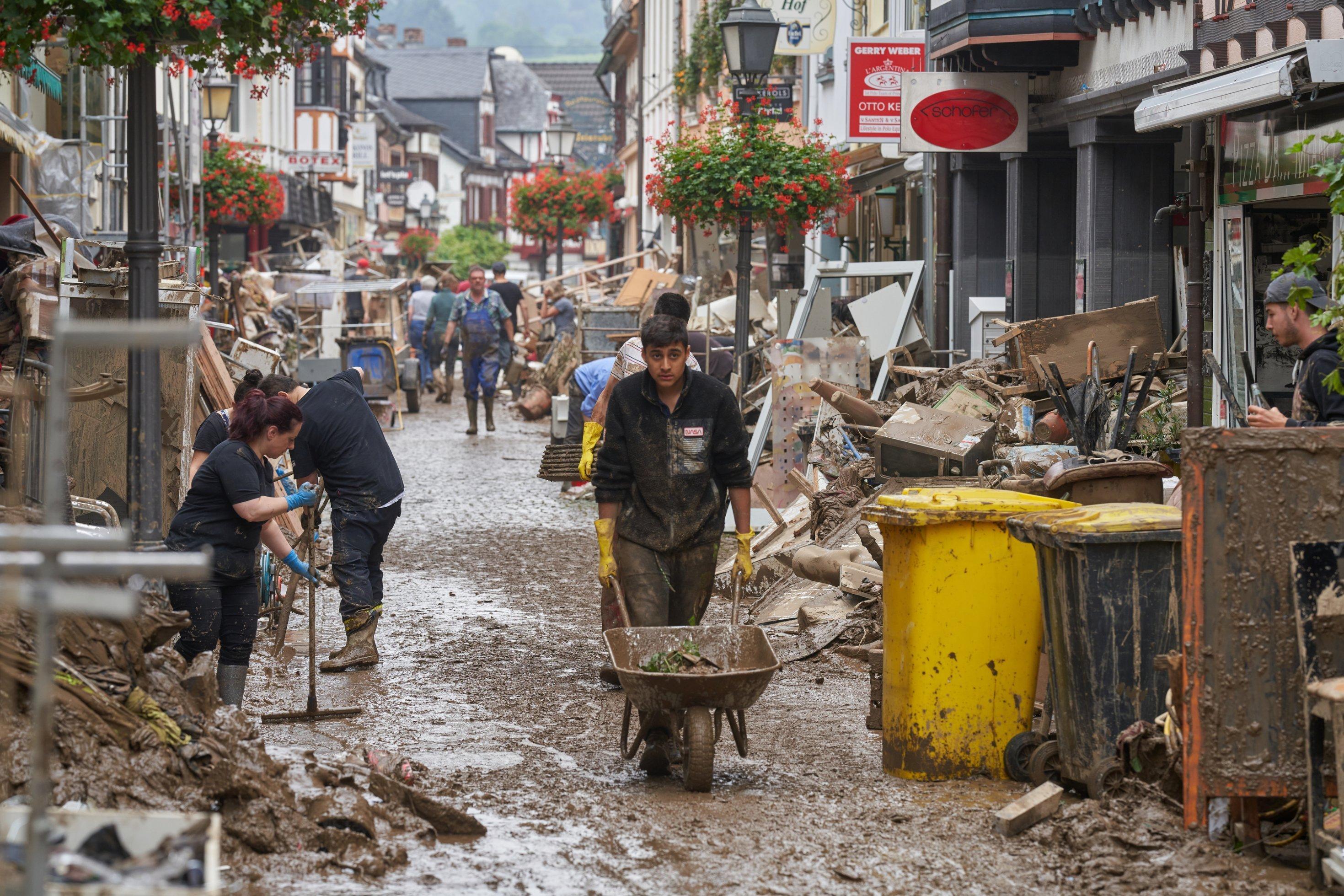 Ein junger Mann schiebt eine Schubkarre durch durch Fußgängerzone, die komplett mit Schutt und Abfall gefüllt ist, im Hintergrund weitere Menschen bei Aufräumarbeiten.