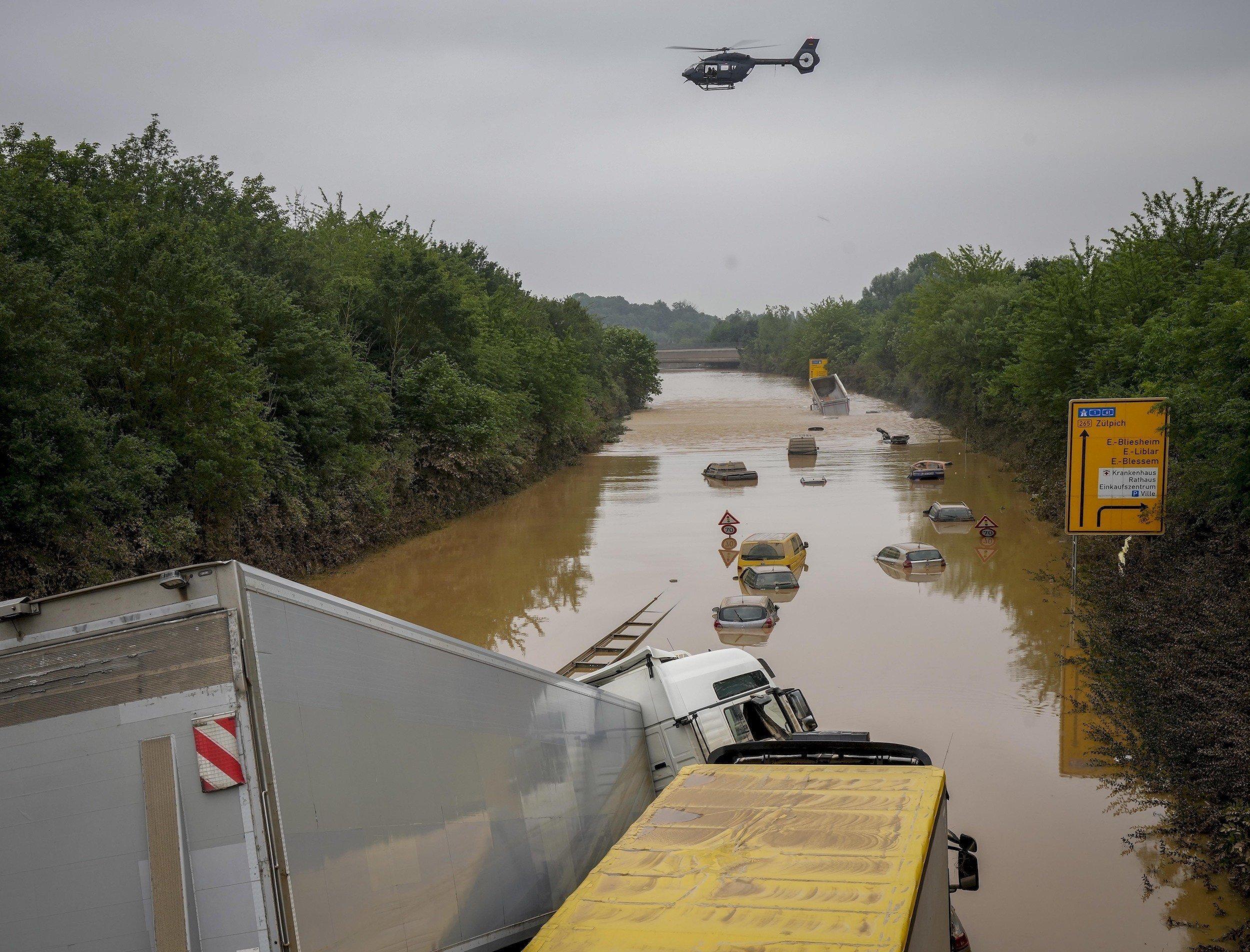 Die Bundesstraße ist komplett überschwemmt, leere Autos stehen im Wasser.