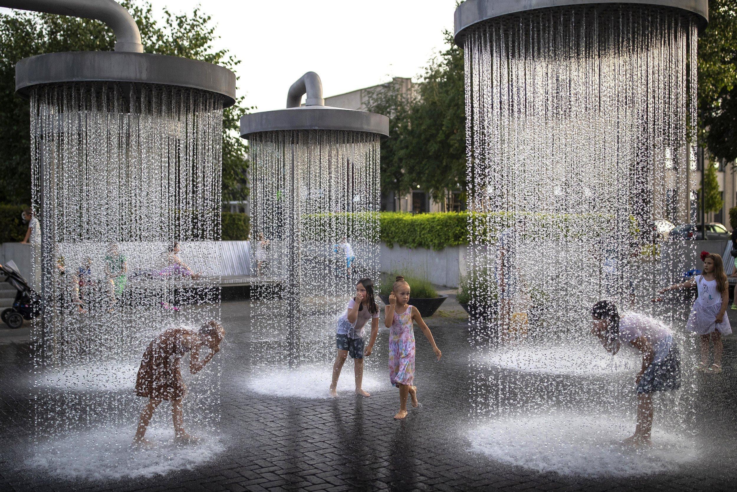 Kinder spielen unter riesigen Duschen, die im Stadtraum von Vilnius installiert sind.