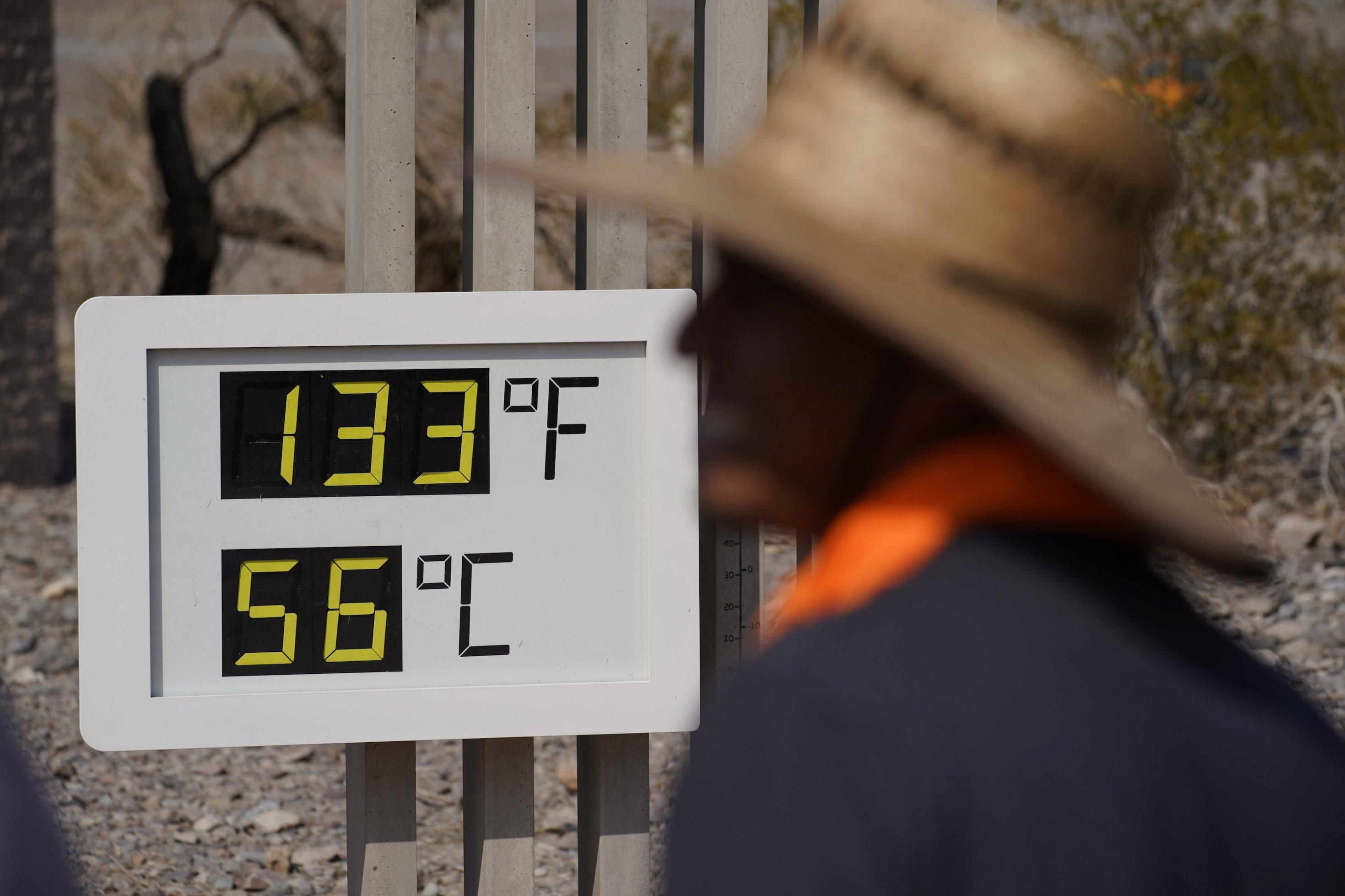 Outdoor-Thermometer zeigt 56Grad, im Vordergrund ein Mann mit Hut.