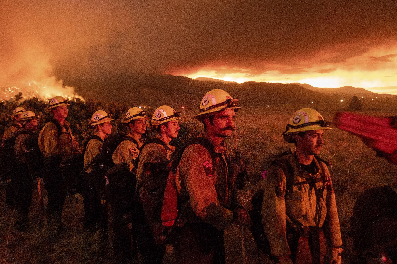 Vom Feuerschein in orange getauchte Feuerwehrleute stehen in einer Reihe und schauen ängstlich drein.