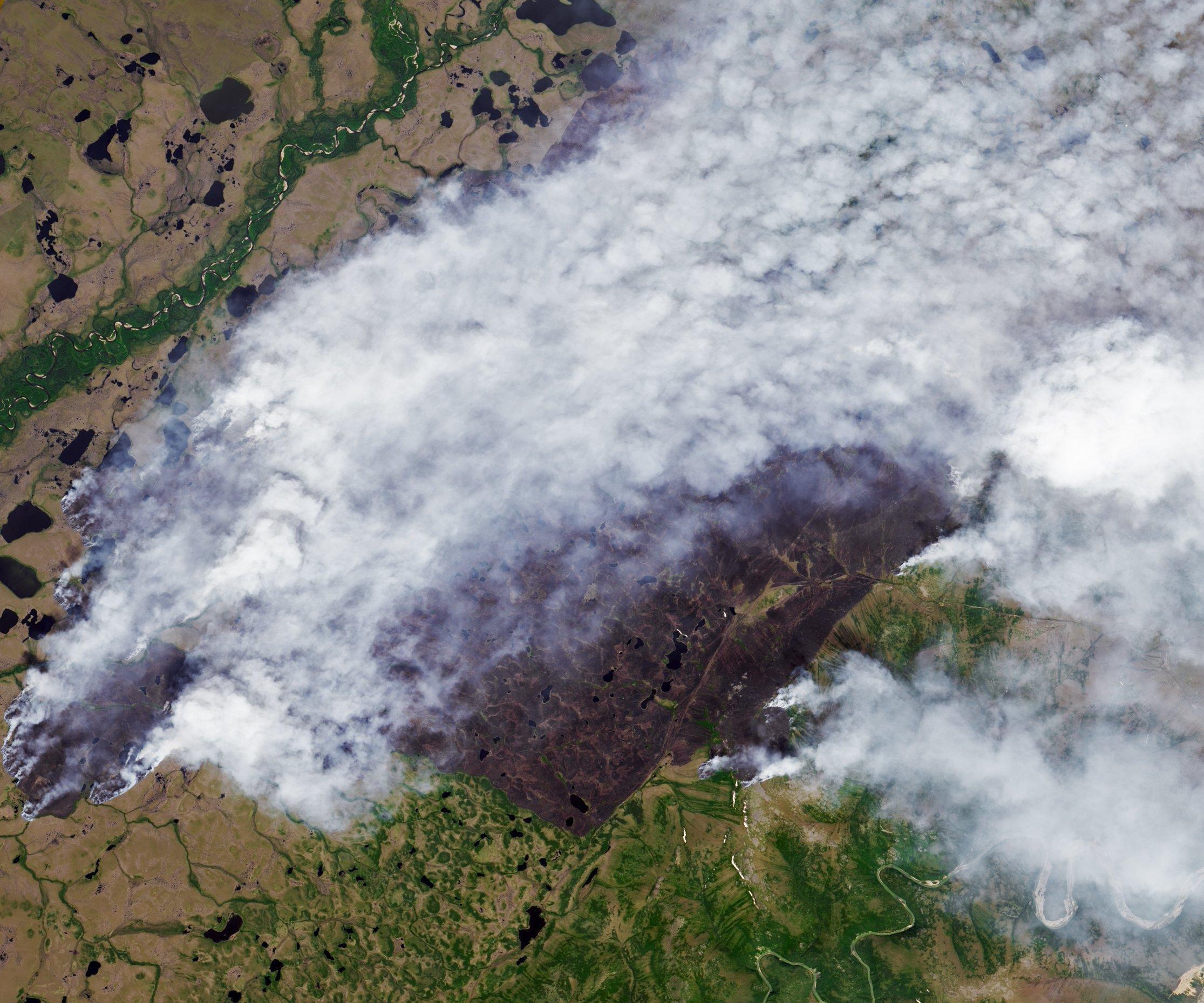Satellitenaufnahme das ein Gebiet von ca. 27×27Kilometern zeigt, auf dem die Erde von Feuern raucht.