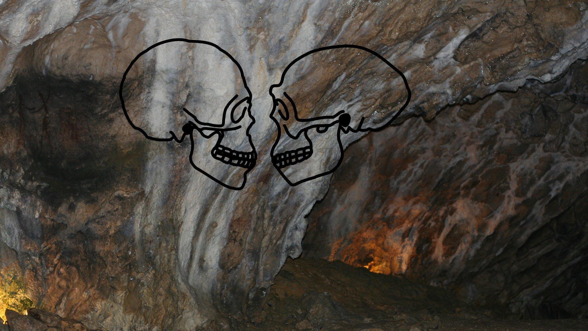 Blick auf die geheimnisvoll leuchtende Wand der Hohle Fels-Höhle in der Schwäbischen Alb. Hier fanden einst frühe Vertreter des Homo sapiens, aber auch andere Urmenschen ein Zuhause. Auf die Felswand projiziert sind die Schädelumrisse eines Homo sapiens und eines Homo erectus, die sich gegenseitig anschauen.