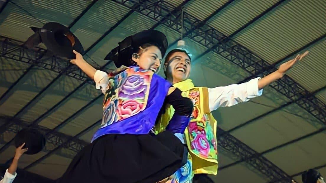 Ein junger Mann und eine junge Frau auf einer Bühne. Beide mit farbenfroh bestickten Rock bzw. Weste und schwarzem Hut. Der Mann hält den Hut in der Hand. Blicken lachend von der Bühne herunter.