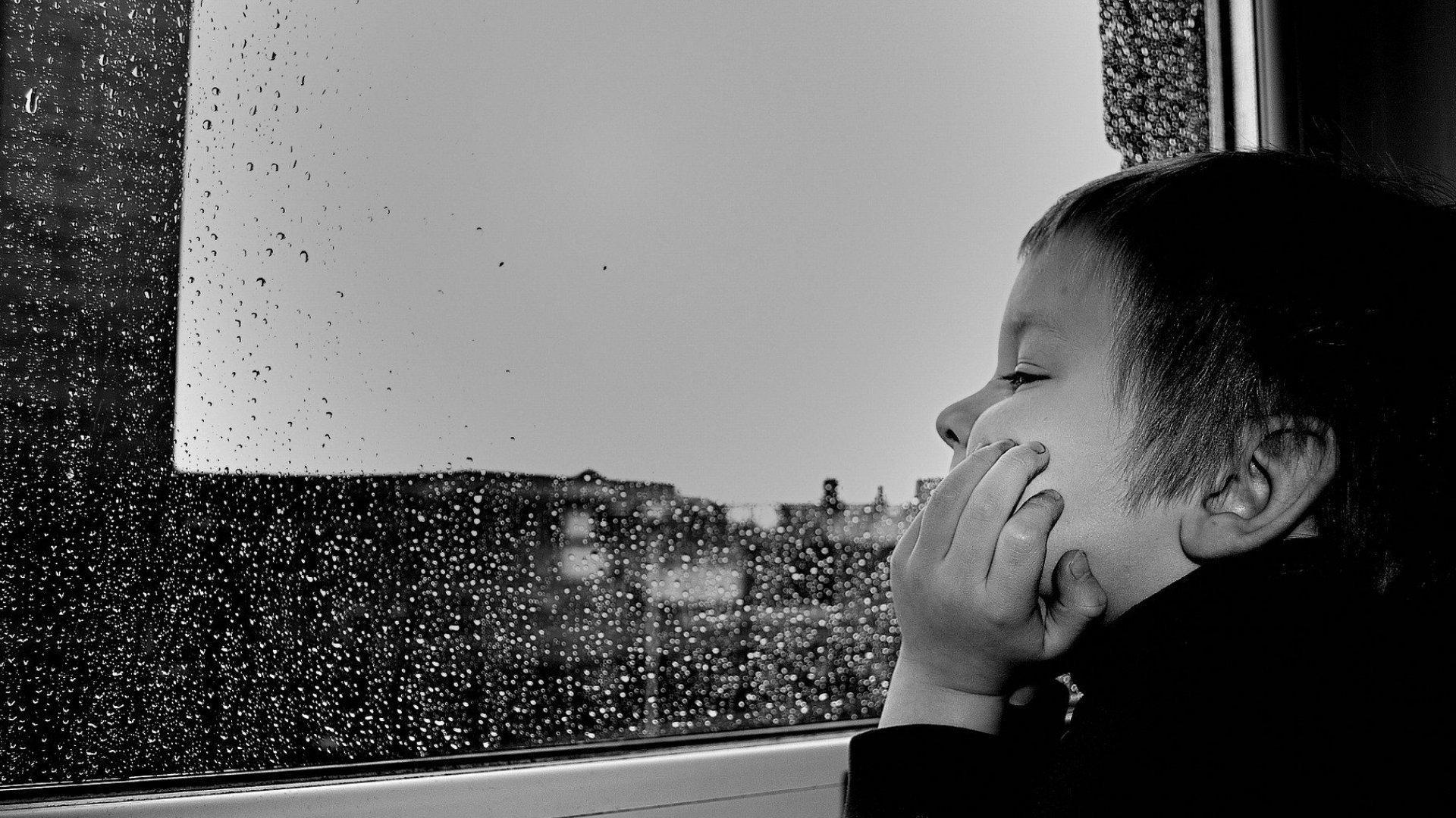 Ein Junge schaut aus einem Fenster. Draußen regnet es, Regentropfen auf der Scheibe.