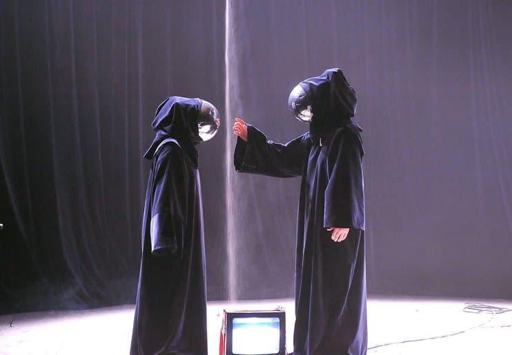 """Zwei in schwarze Kutten gehüllte Gestalten stehen sich auf runder, heller Bühne vor dunklem Hintergrund gegenüber. Zwischen ihnen rieselt ein feiner Strahl Sand herab. Die rechte Gestalt hebt eine Hand zum Gesicht ihres Gegenübers – aber da ist nichts. Unter den Kapuzen """"starren"""" zwei silberne Kugeln sich gegenseitig an."""