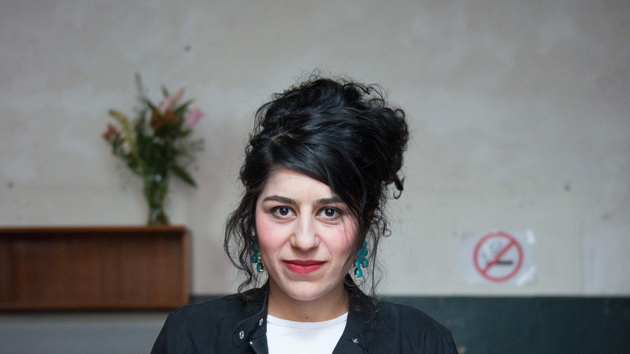 Sahar Rahimi blickt in Jeans, weißem Shirt und schwarzer, cooler Jacke gerade und entschlossen in die Kamera. Im Hintergrund nackte Betonwand und dunkle Möbel, oben ein schmaler Strauß Blumen in einer hohen Vase. Sie hat ihre dunklen, lockigen Haare aufgetürmt und ist geschminkt mit Rouge, Lippenstift und Nagellack. In ihrer rechten Hand hält sie eine beige Handtasche, auf den ersten Blick sieht das aus wie ein Buch. In ihrer linken Hand hält sie ein Gläschen Hipp-Babynahrung. Auf den ersten Blick denkt man, es sei eine Dose Cola oder ähnliches.