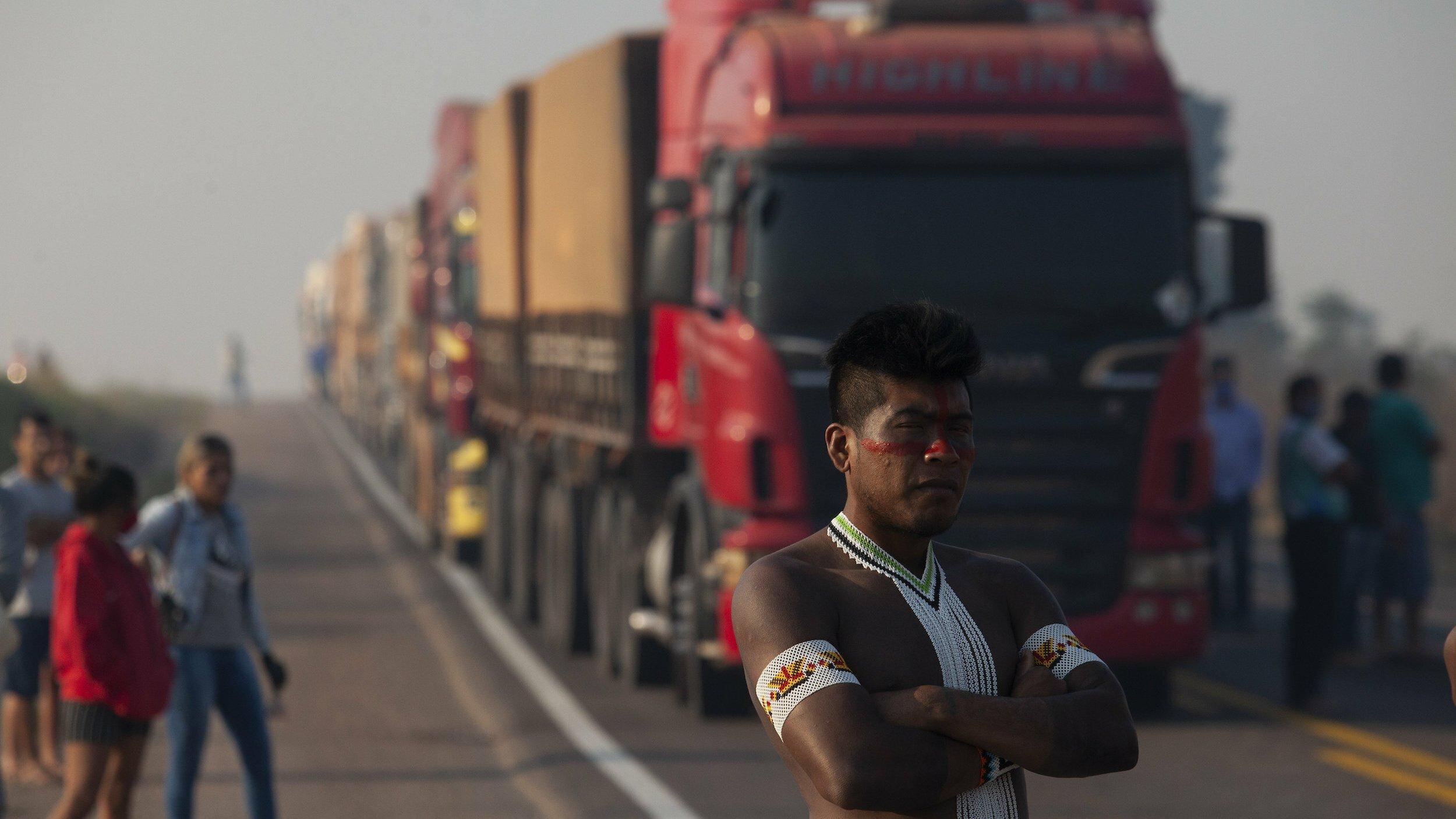 Ein indigener Mann steht mit geschlossenen Augen mitten auf der Straße, hinter ihm stauen sich LKW.
