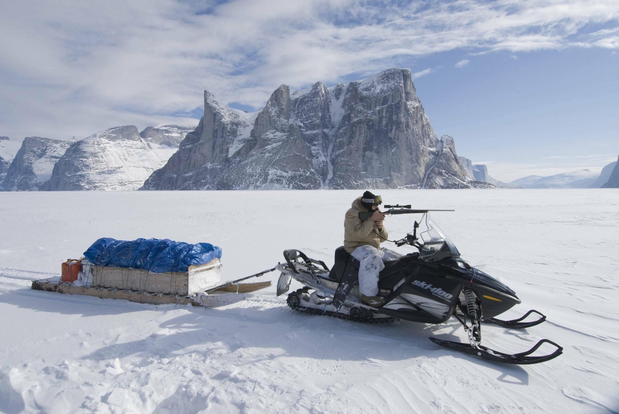 In einer schneebedeckten Landschaft mit hohen Bergen sitzt ein Inuit auf einem Motorschlitten und zielt mit einem Gewehr in die Ferne.