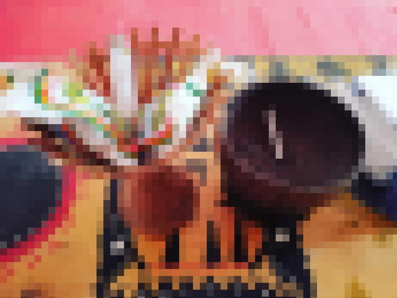 Auf einem mit geometrischen Mustern verziertem Tisch steht ein Aschenbecher aus Kokosnuss und ein geflochtener Korb mit zwei Plastiktütchen voll Tabak und einem Feuerzeug.