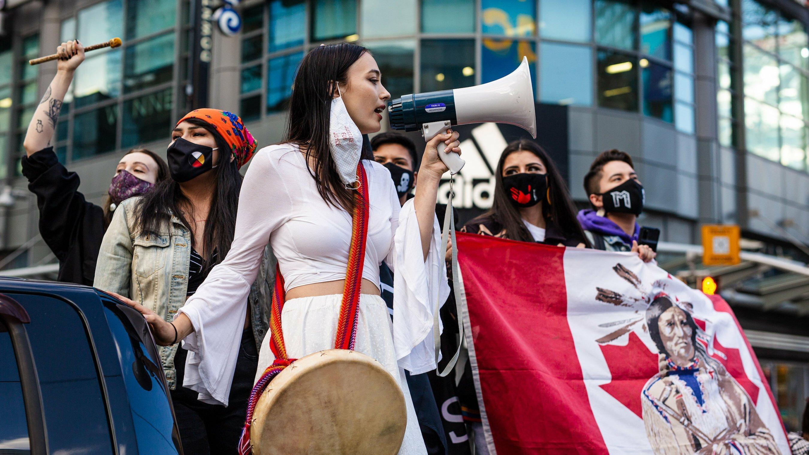 Junge Demonstrantinnen der kanadischen Indigenen stehen in einer Gruppe und halten ein Transparent mit der kanadischen Flagge, auf der ein indigener Häuptling zu sehen ist. Eine junge Frau in weißem Kleid spricht in ein Megafon.