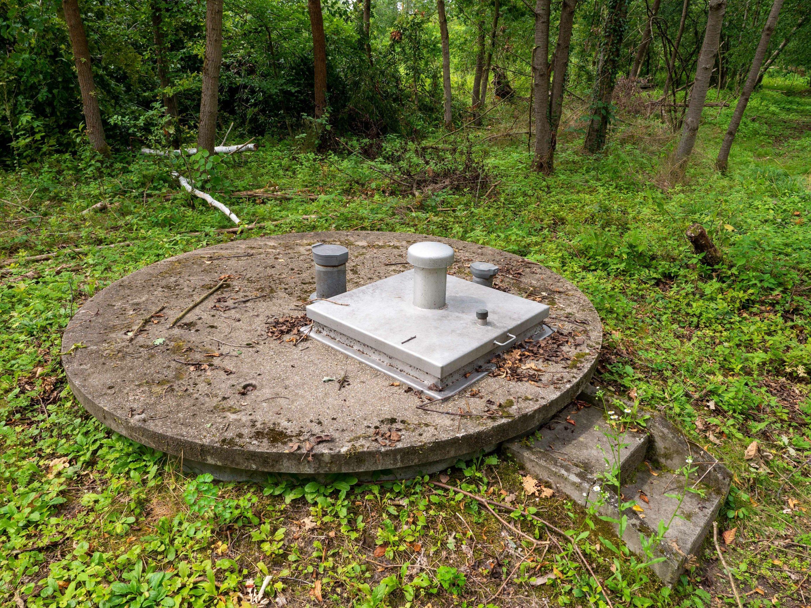 Runder Betondeckel mit pilzformogem Belüftungsstutzen leicht erhöht übder dem Boden eines Waldes