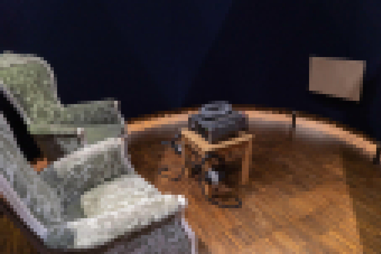 Zwei Sessel mit grün geblümtem Muster stehen vor einem Tisch, auf dem ein Gerät zum Abspielen der Klanginstallation steht.