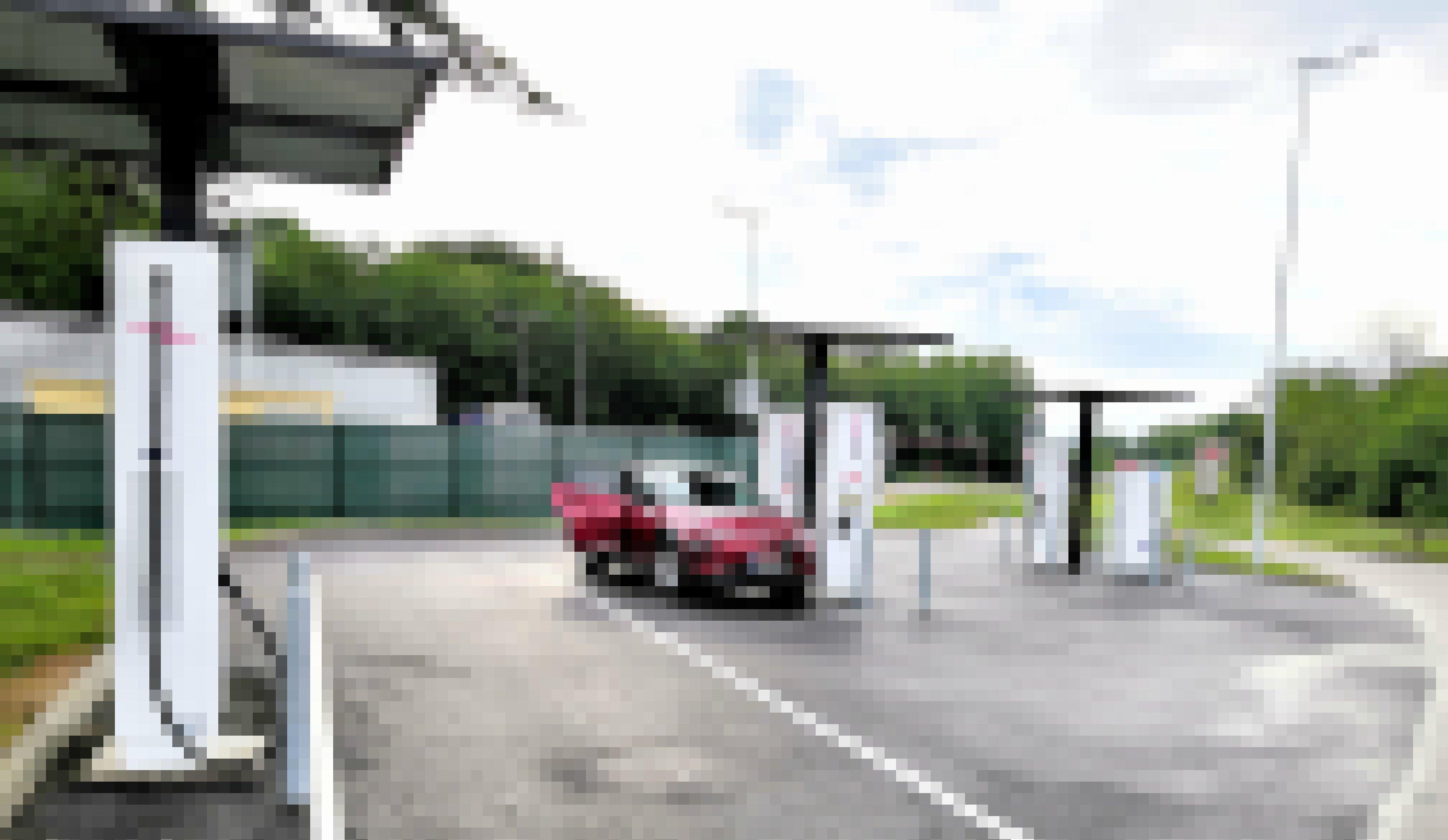 Ein Elektroauto steht auf einem Rastplatz und ist mit einer Ladesäule verbunden.