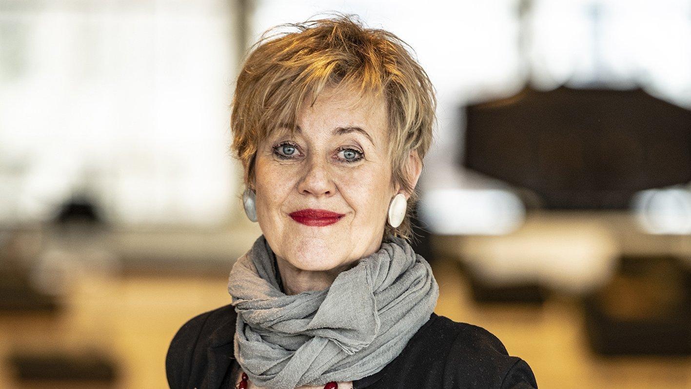 Porträtfoto von Iris ter Schiphorst – eine Frau mit kurzen Haaren steht in einem Konzertsaal