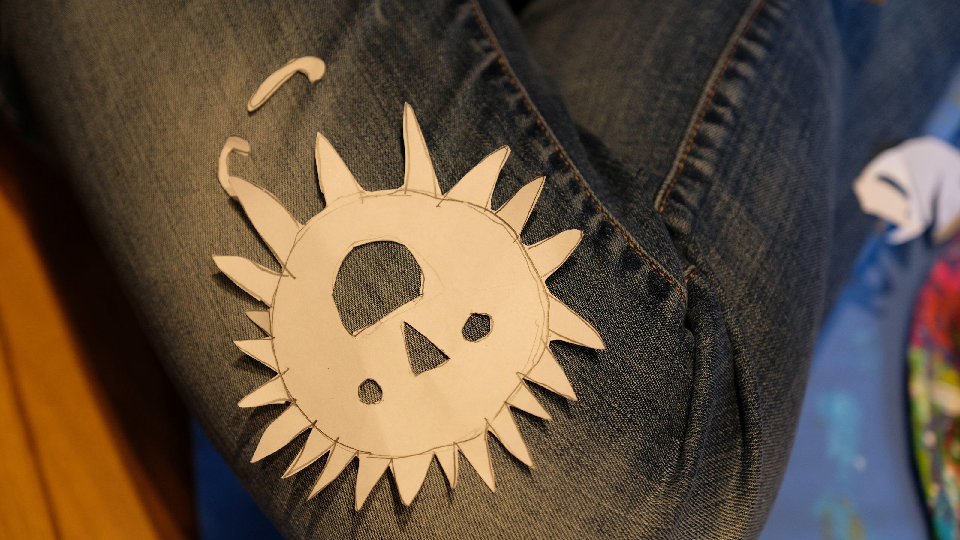 Man sieht nur das angewinkelte Knie von Irma in einer Jeans. Darauf liegt eine ausgeschnittene Sonne mit Augen und Mund.