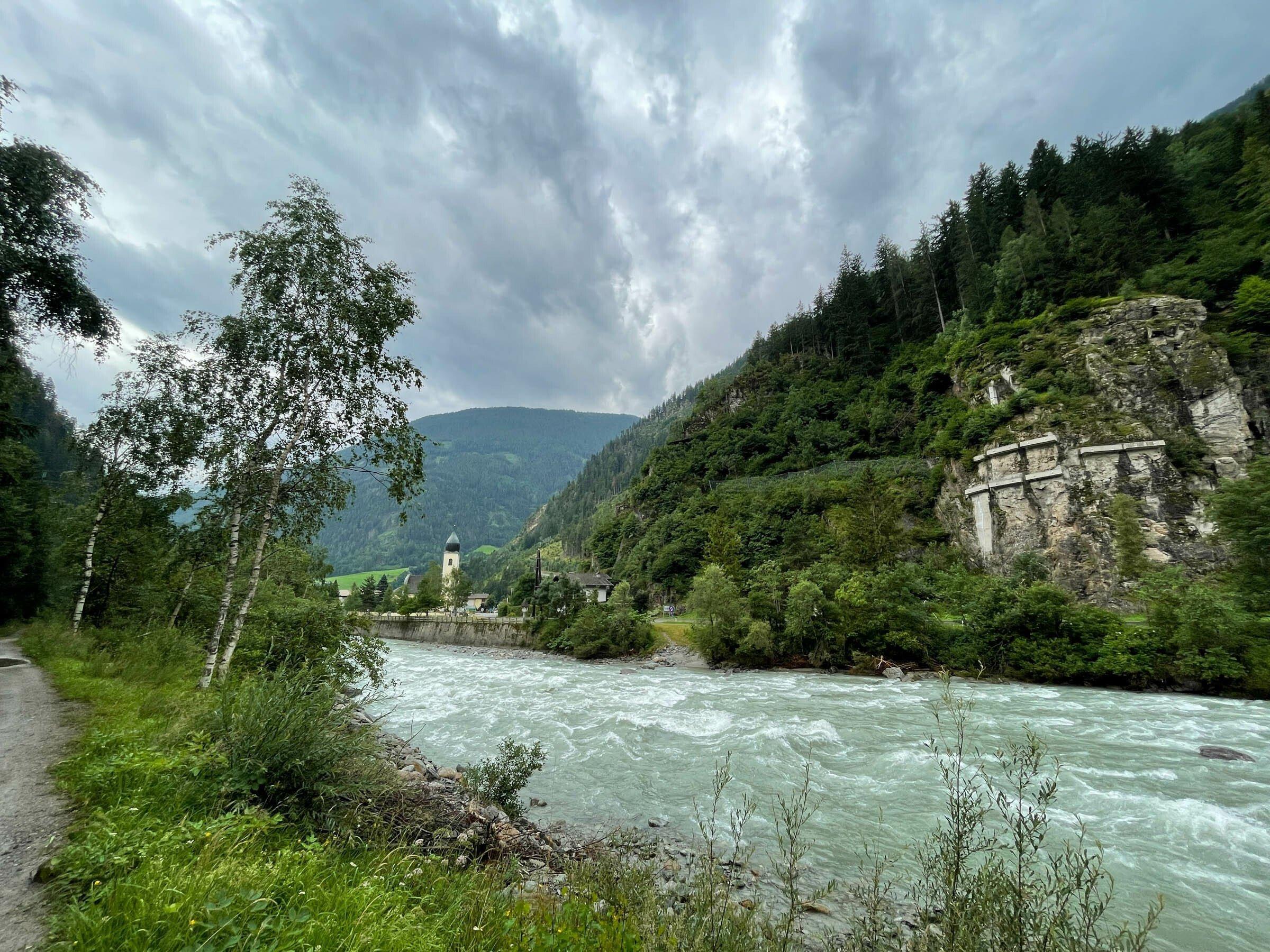 Landschaft mit türkisfarbenem Fluss und grünen Wäldern und Wiesen, Kirchturm.