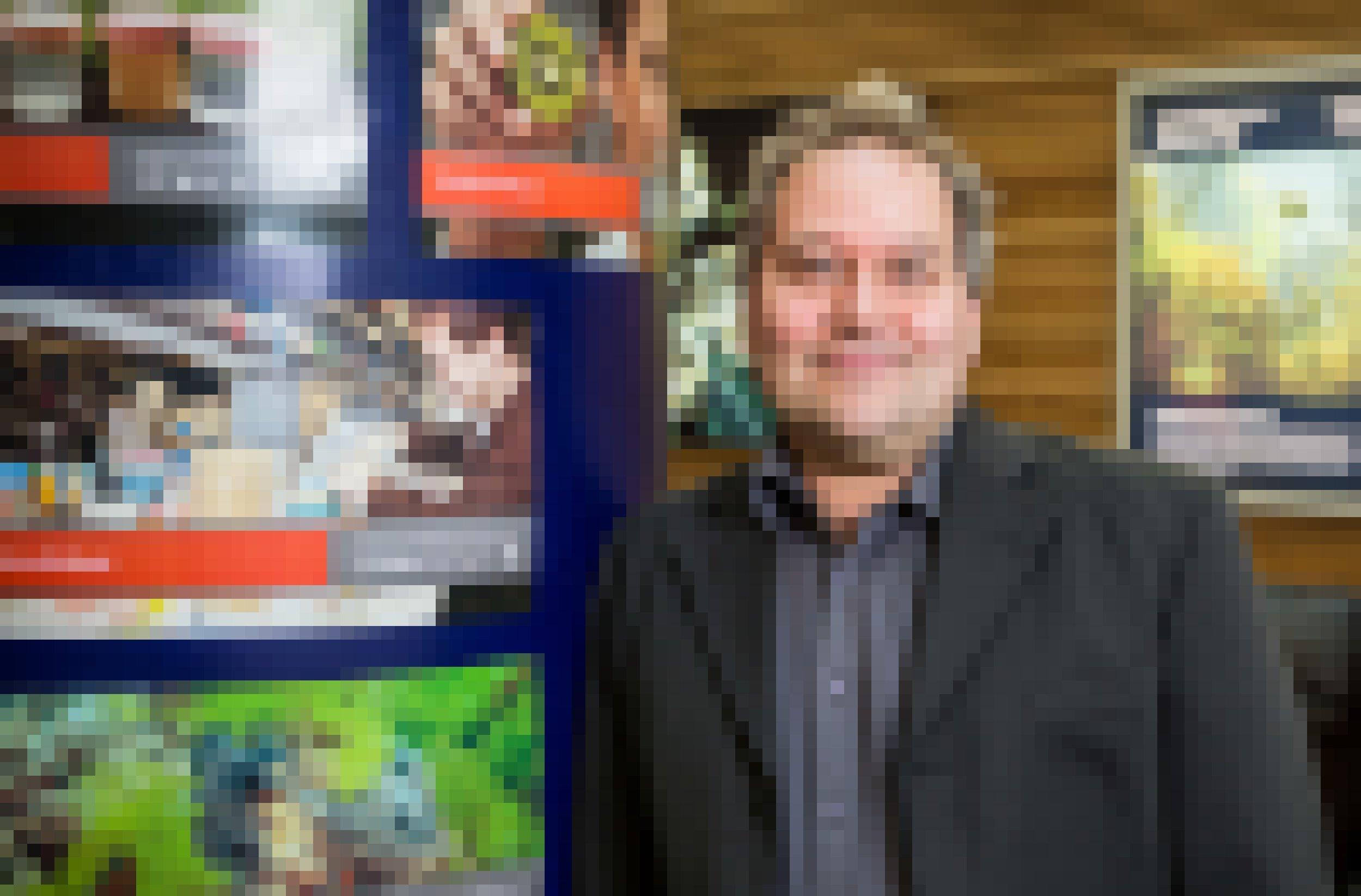 Ein Mann mit kurzem graumeliertem Haar in dunklem Sacko und Hemd lächelt in die Kamera. Er lehnt an einer Säule mit Postern.