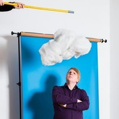 Journalist Jakob Vicari steht vor blauem Hintergrund, er schaut nach oben, denn dort schwebt eine Wolke über seinem Kopf.