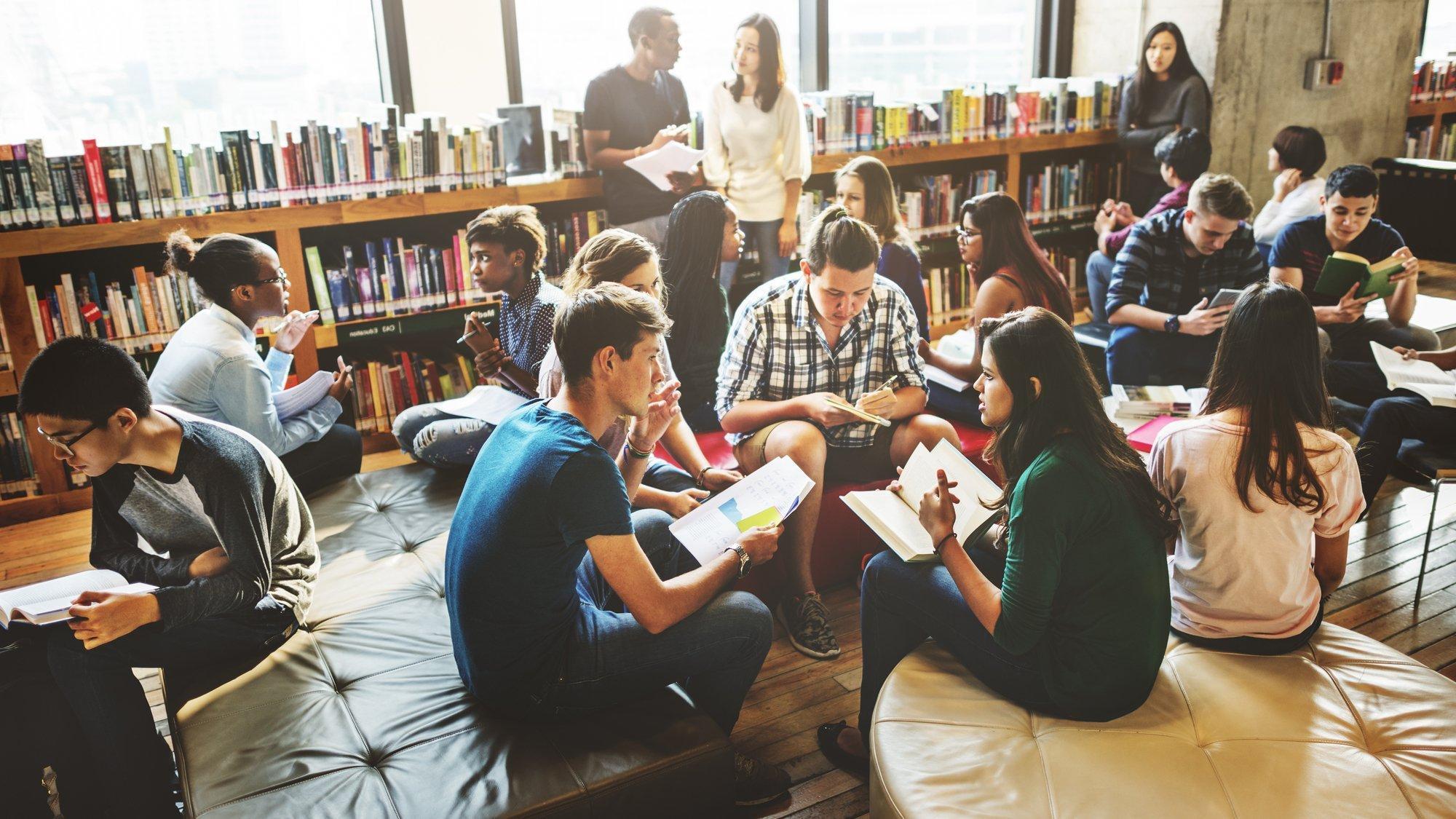 Junge Menschen diskutieren und lernen in einer Bibliothek.