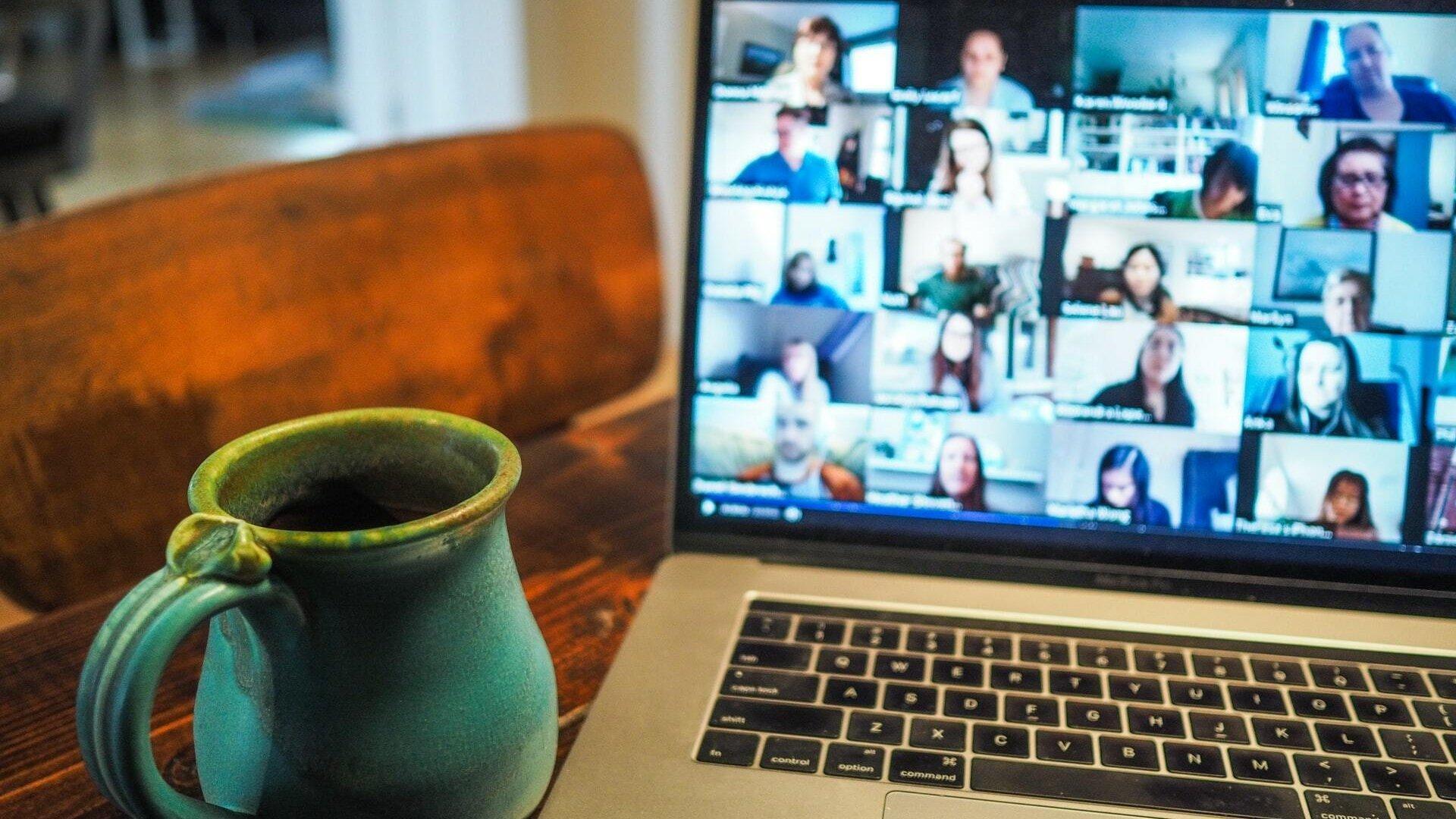 Eine Kaffeetasse steht auf einem Tisch vor einem Laptop. Auf dem Laptop findet eine Videokonferenz statt.