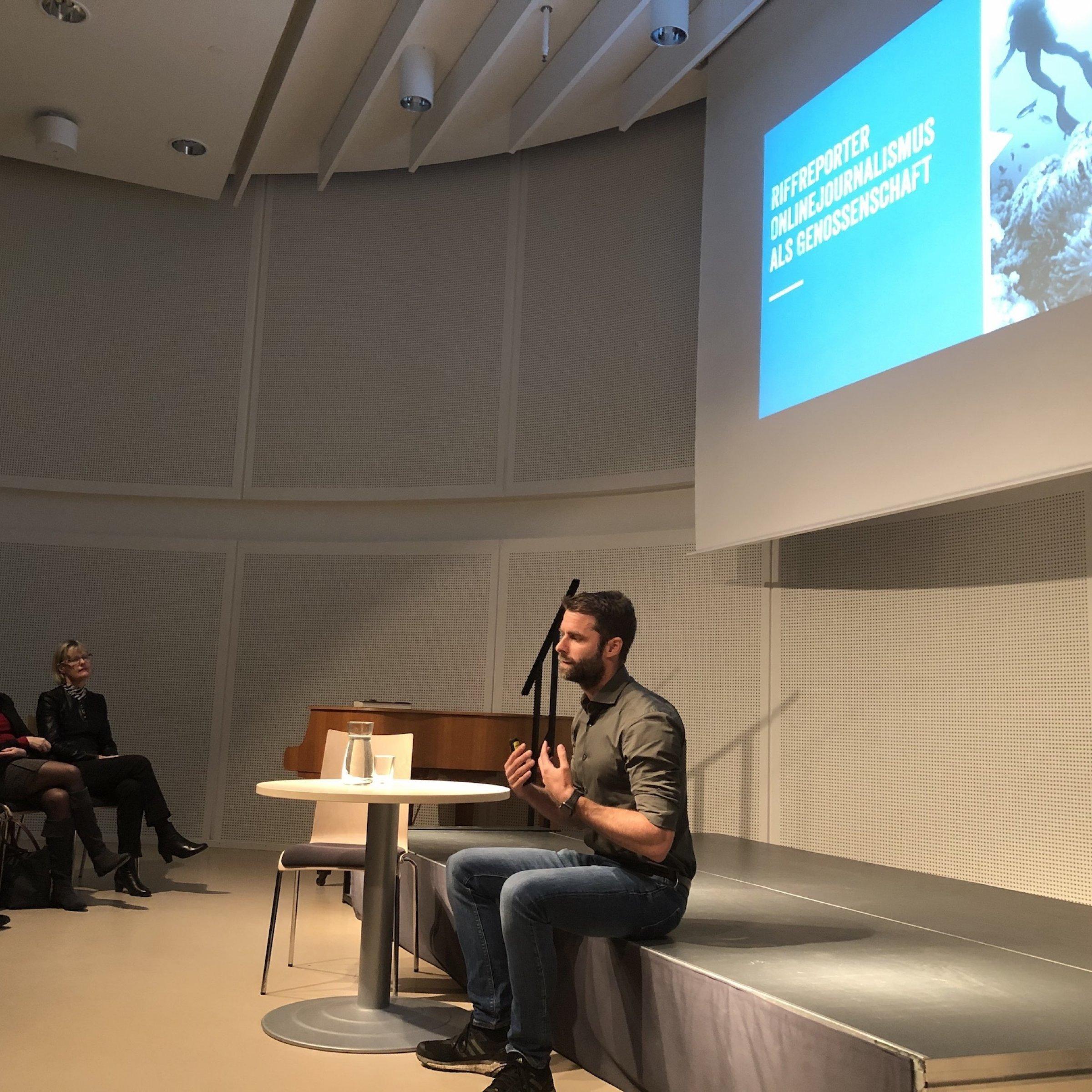 Der Journalist Kai Kupferschmidt sitzt auf einer Bühne und spricht, vor ihm das Publikum der Stadt- und Landesbibliothek Potsdam.