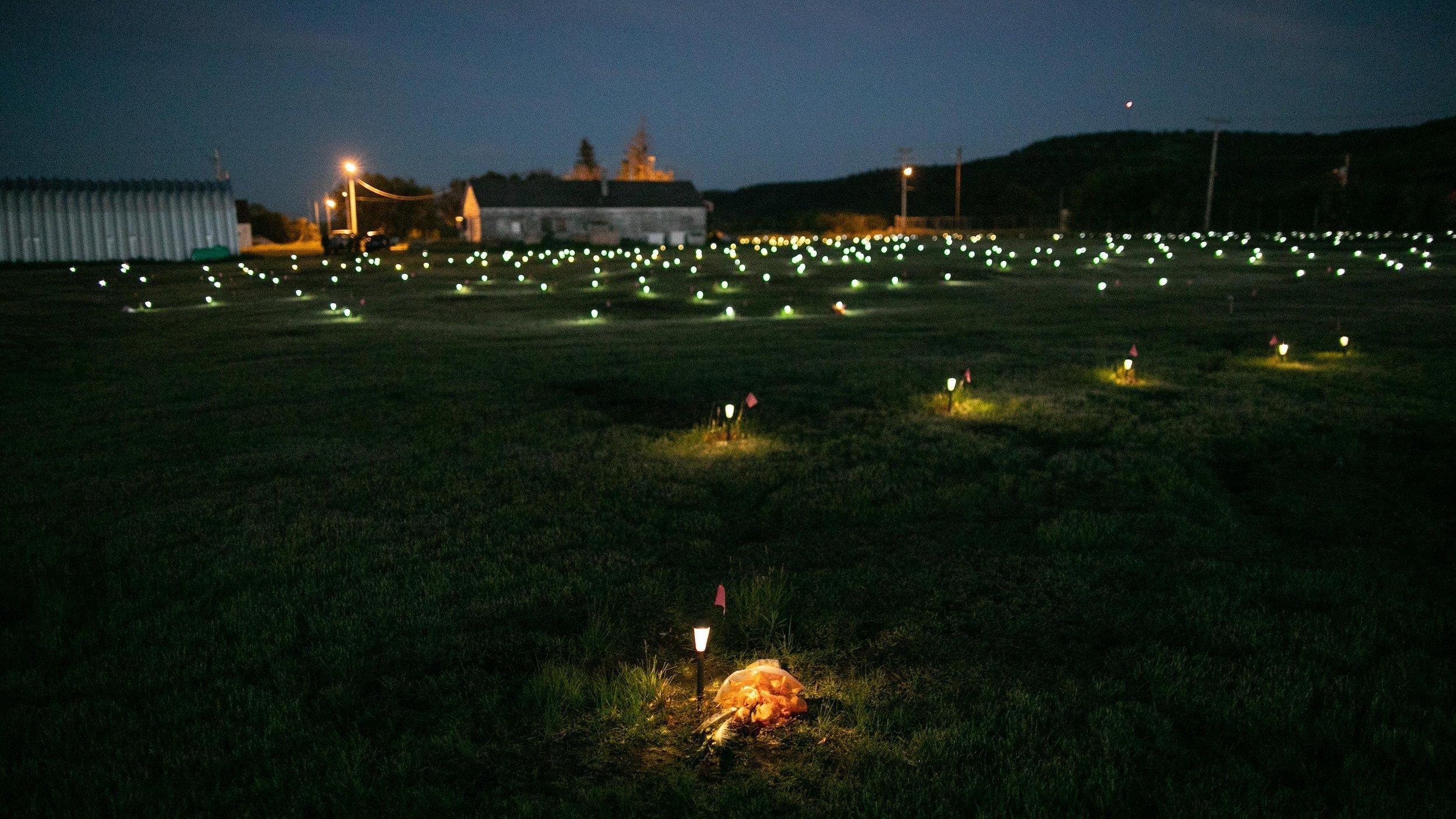 In der Dämmerung leuchten zahlreiche Solarlämpchen auf der Wiese vor einer Kirche, sie markieren die aufgefundenen Kindergräber.
