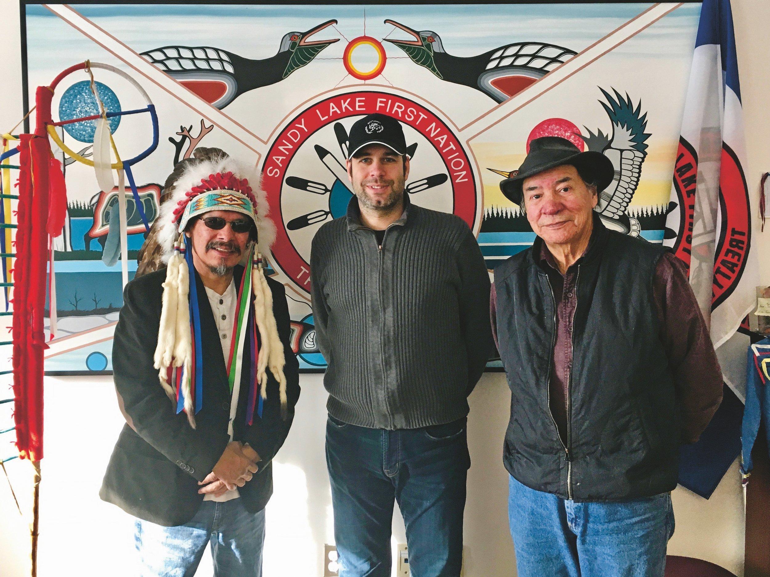 Menrath trägt ein Basecap und steht zwischen den beiden Männern, Chief Meekis trägt traditionelle Kleidung.
