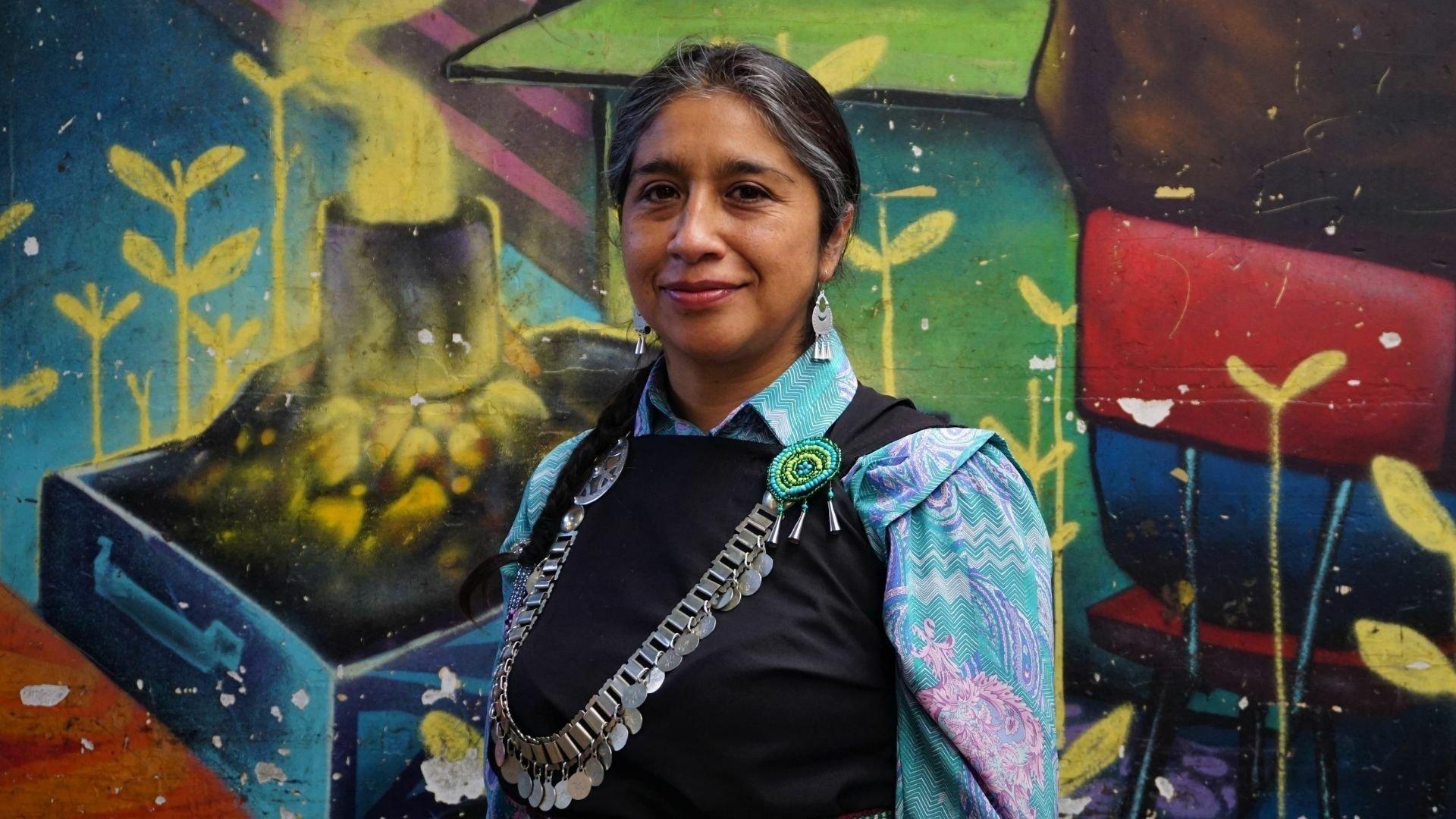 Eine Frau mit schwarzen Haaren und Zopf mit grauen Strähnen steht vor einem Wandbild, das unter anderem Getreide und einen rauchenden Schlot zeigt. Sie trägt unter einem schwarzen Oberteil eine bunt gemusterte Bluse, Silber-Ohrringe und eine breite Silberkette über der Brust.