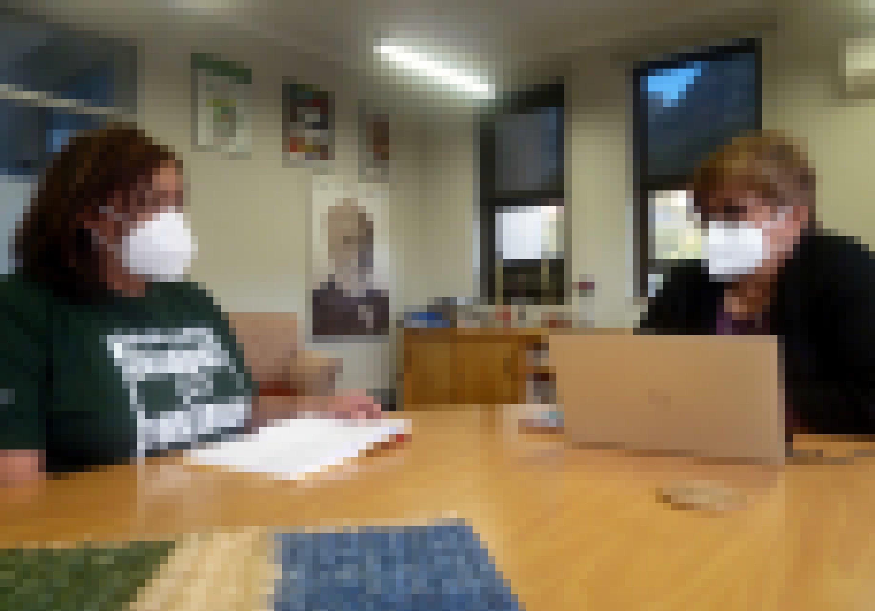 Die beiden Frauen sitzen mit Mund-Nasenschutz an einem Tisch und besprechen die weiteren Schritte