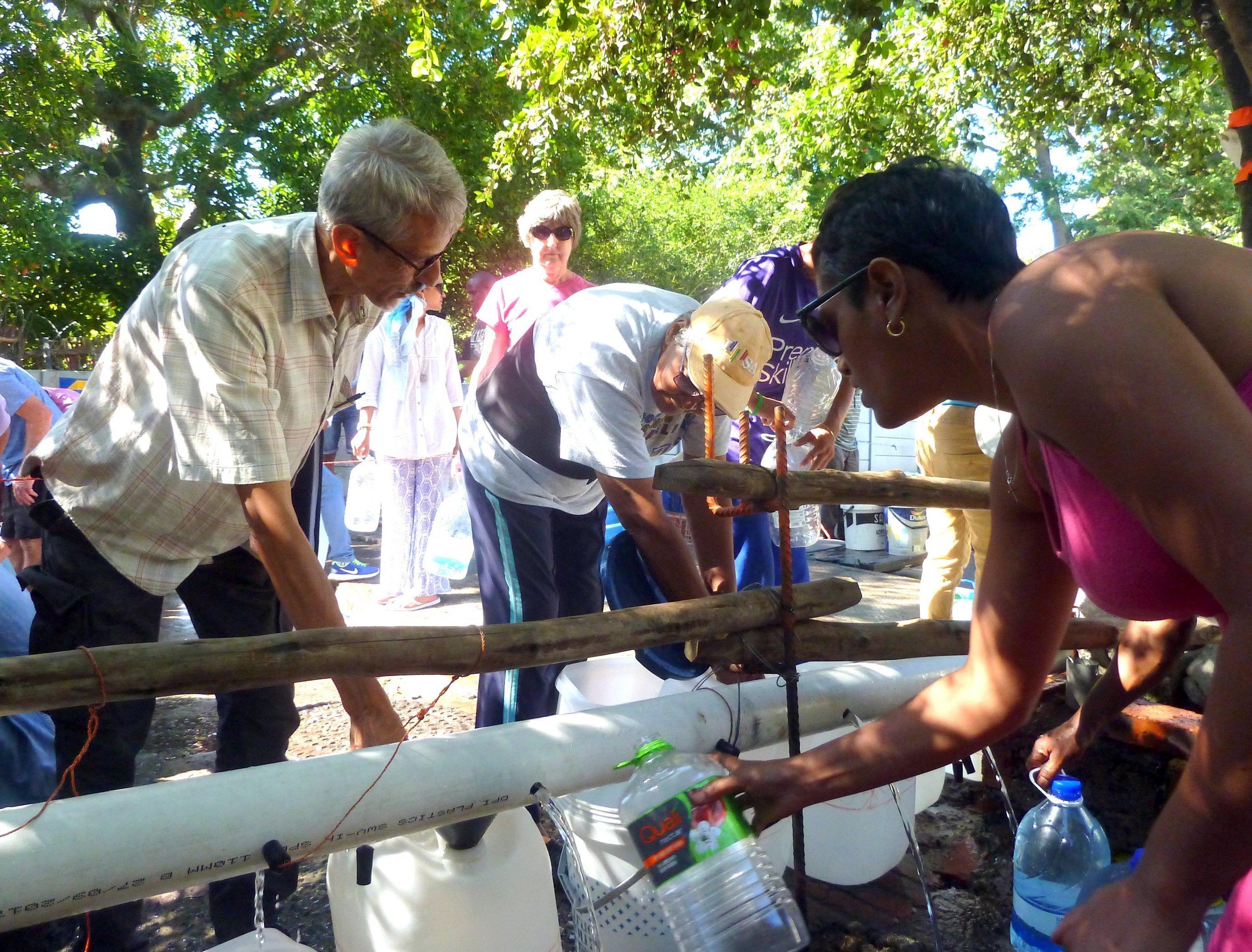 Männer und Frauen zapfen Quellwasser in mitgebrachte Behälter, andere warten bis sie an der Reihe sind