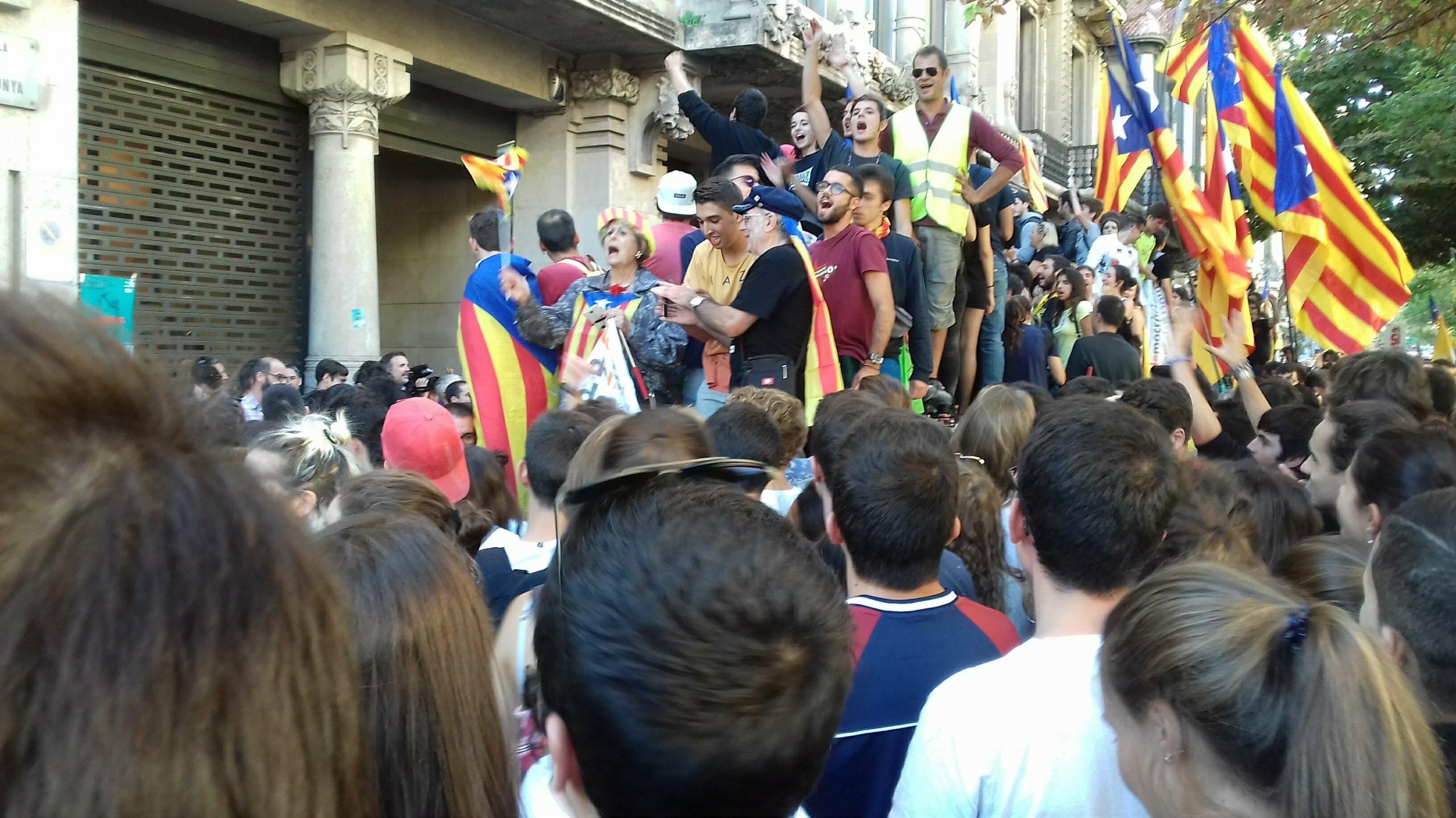 Menschen mit katalanischen Pro-Unabhängigkeitsfahnen demonstrieren vor dem katalanischen Wirtschaftsministerium gegen polizeiliche Durchsuchungen.