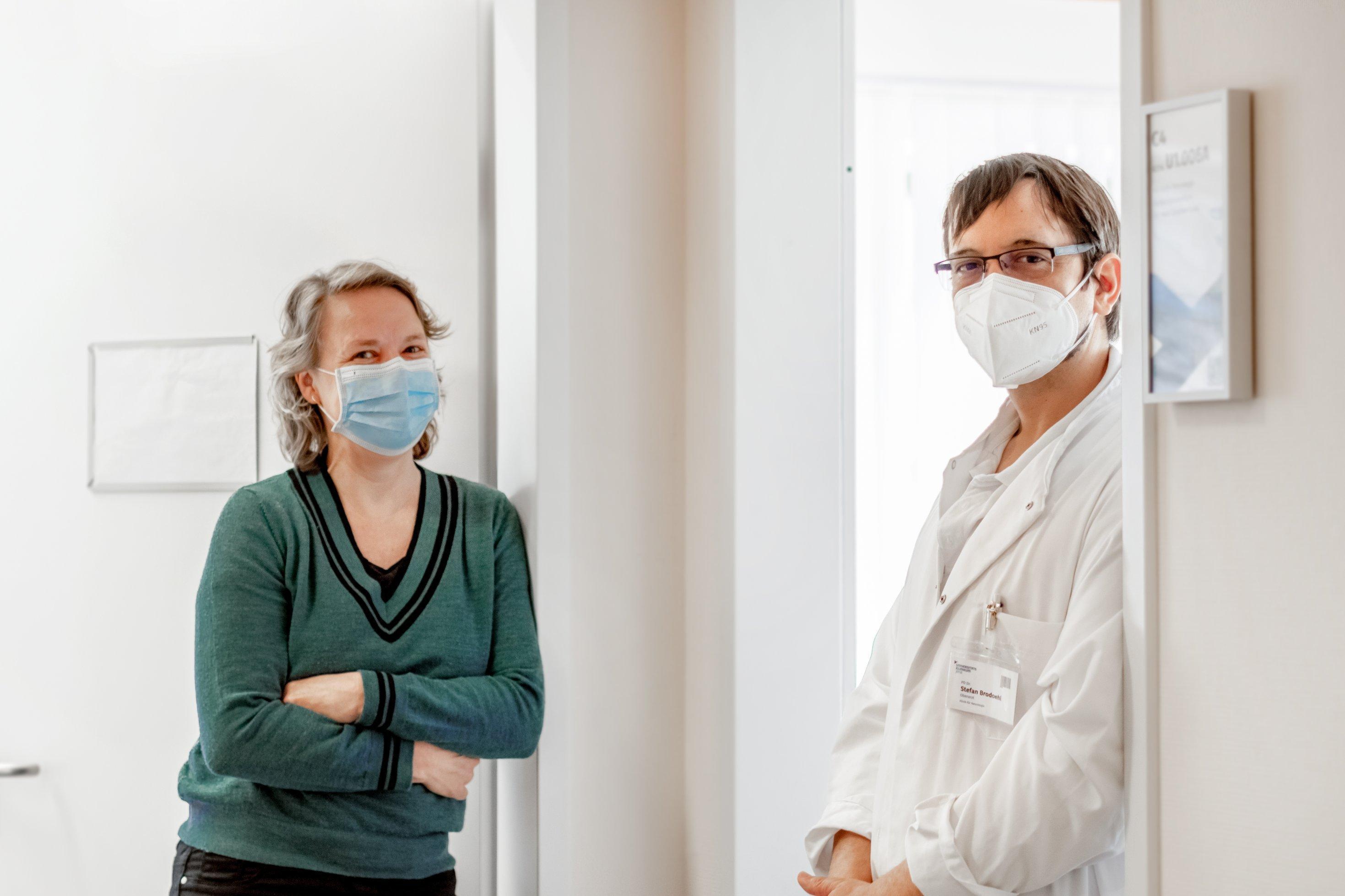 Eine Frau und ein Mann stehen an einer Tür angelehnt, beide tragen einen Mund-Nasenschutz. Die Therapeuten kümmern sich um Long Covid Patienten.