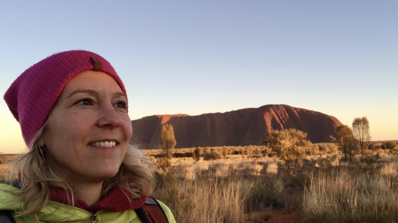 Das Bild zeigt Katja Trippel bei Sonnenaufgang vor dem Uluru
