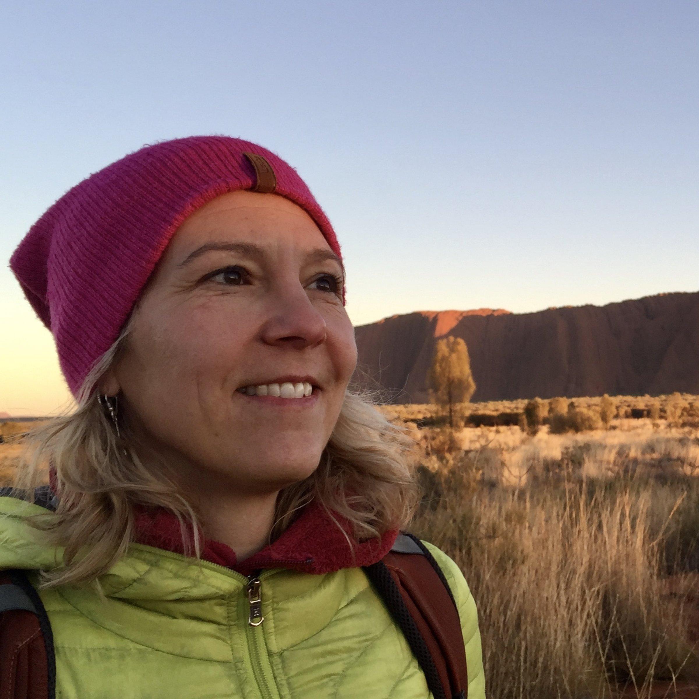 Das Bild zeigt Katja Trippel bei Sonnenaufgang vor dem Uluru.
