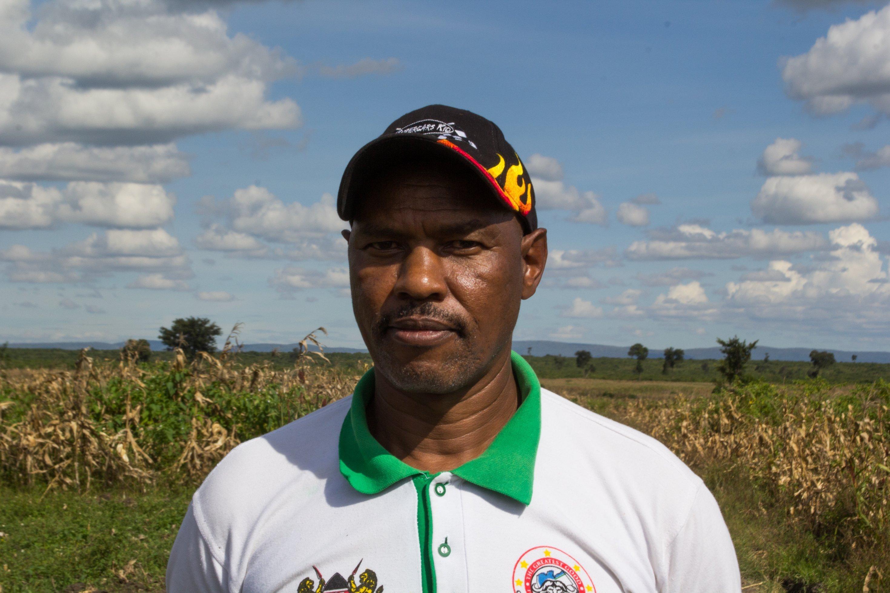 Cherus Korir trägt T-Shirt und Baseball-Kappe, er sieht jung und nicht sehr formell aus. Er steht auf einem Maisfeld, auf Land, das eigentlich zum Mau-Wald gehört.