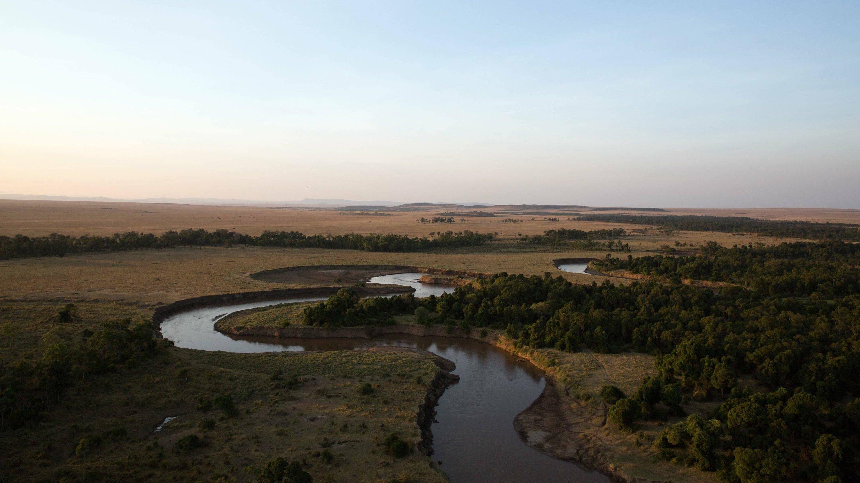Die Aufnahme wurde aus der Luft gemacht, im Abendlicht. Zu sehen sind der Mara-Fluss und die Weite des Nationalparks.