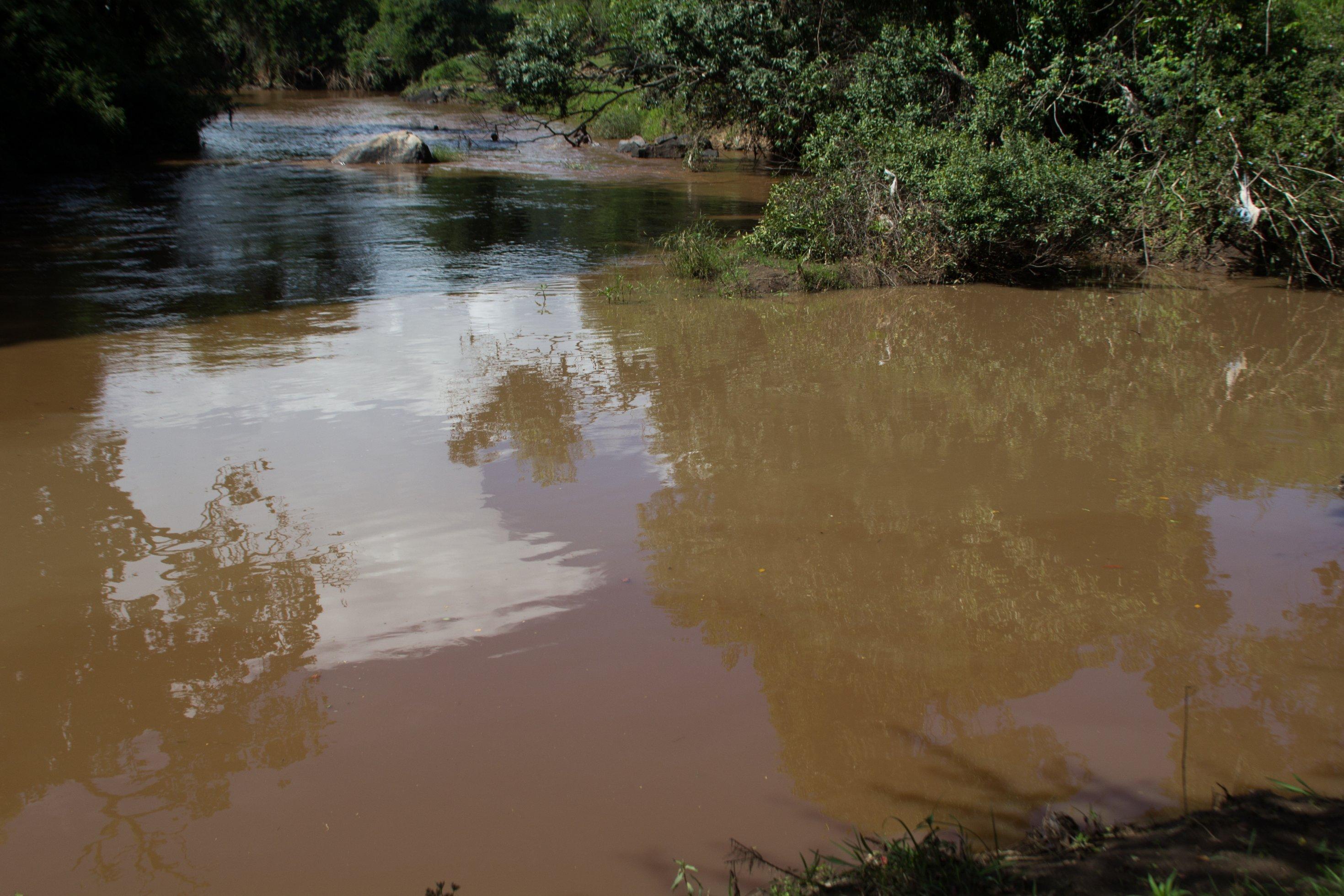 Ein Blick auf den Amala, er ist rotbraun. Im Wasser spiegeln sich trotzdem die Wolken.