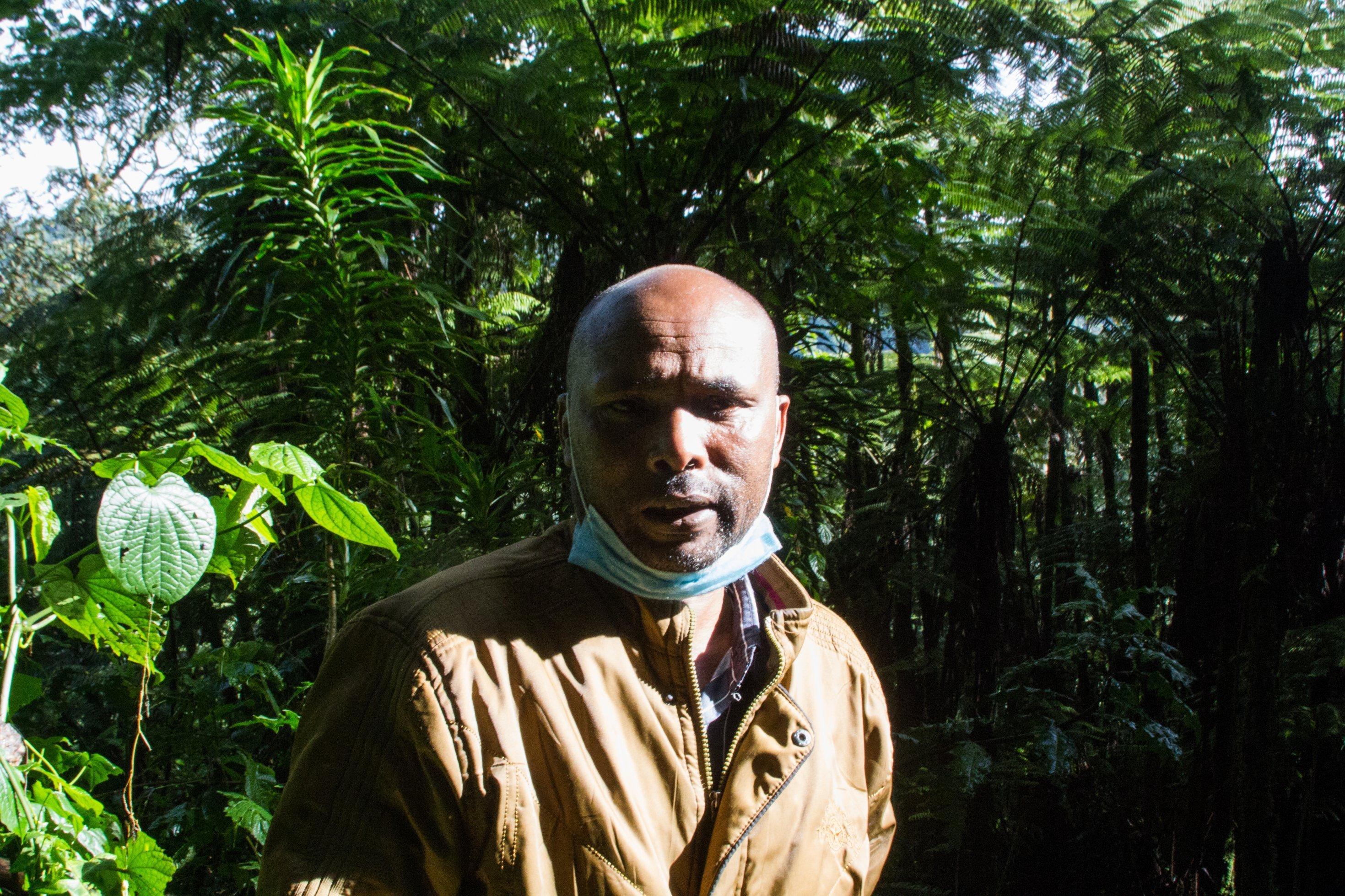 John Mutai im Sonnenlicht, im Hintergrund der Regenwald zu sehen.